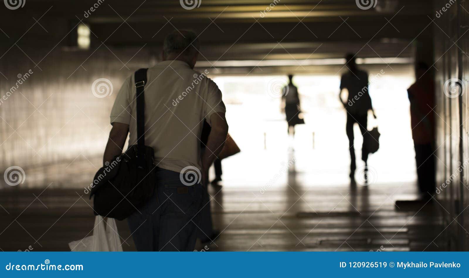 Sylwetki ludzie chodzi w ciemnym tunelu przeciw białej łunie