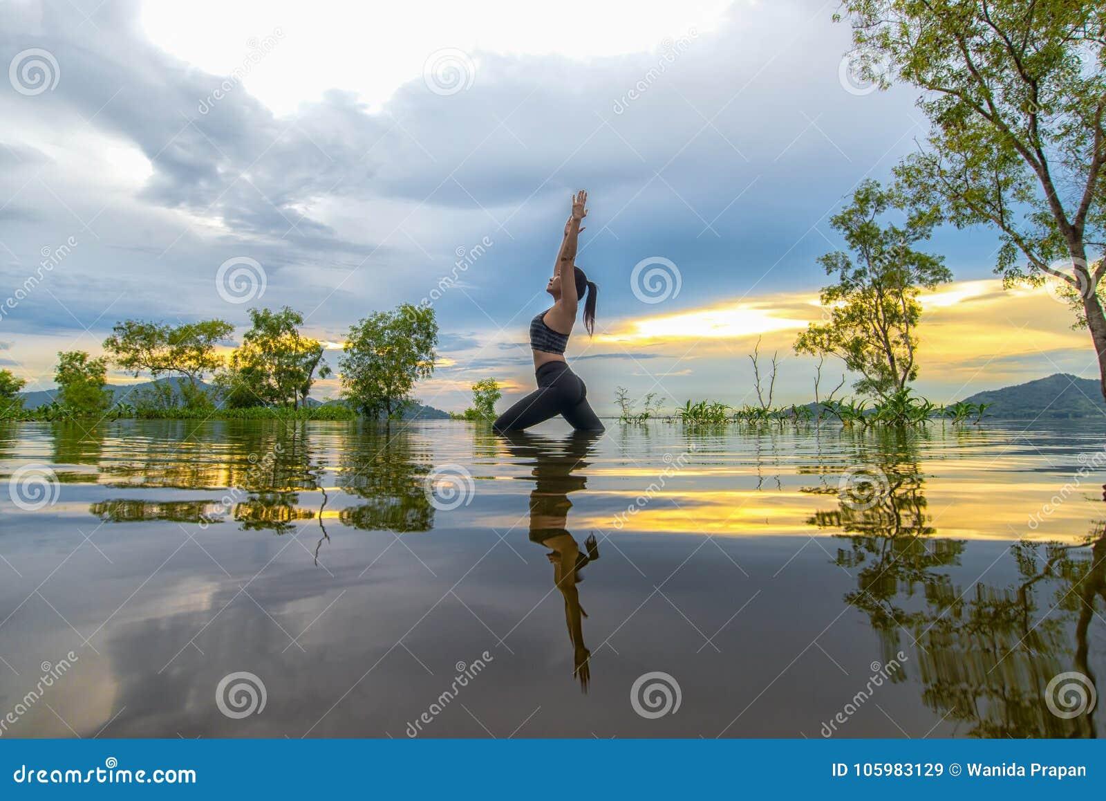 Sylwetki młodej kobiety stylu życia ćwiczyć zasadniczy medytuje i ćwiczyć odbija na wodnej powodzi drzewa w rezerwuarze, backgr