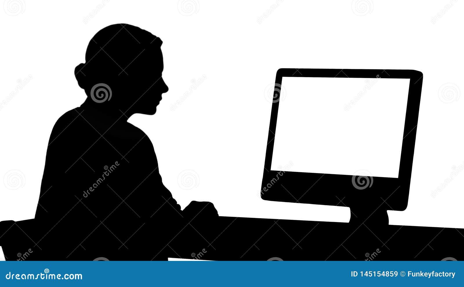 Sylwetki m?oda kobieta pracuje w biurze, siedz?cy przy biurkiem, patrzeje monitoru