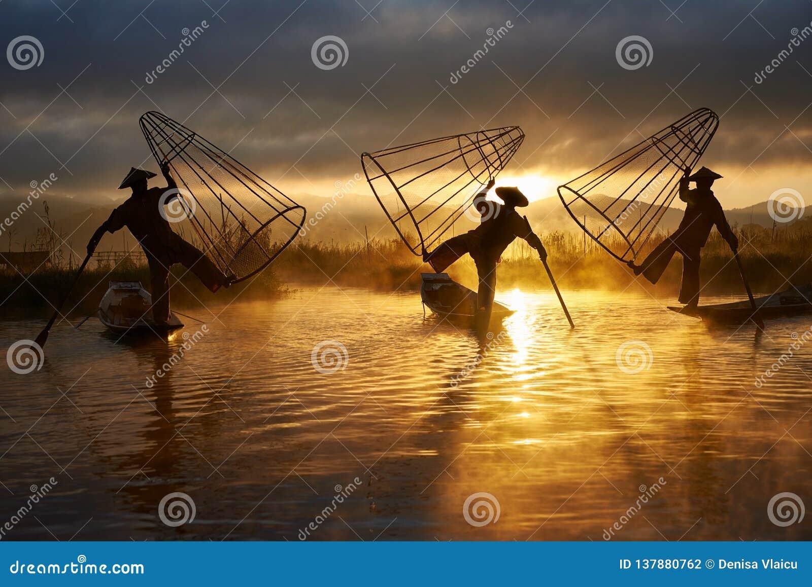 Sylwetki trzy rybaka na Inle jeziorze Myanmar