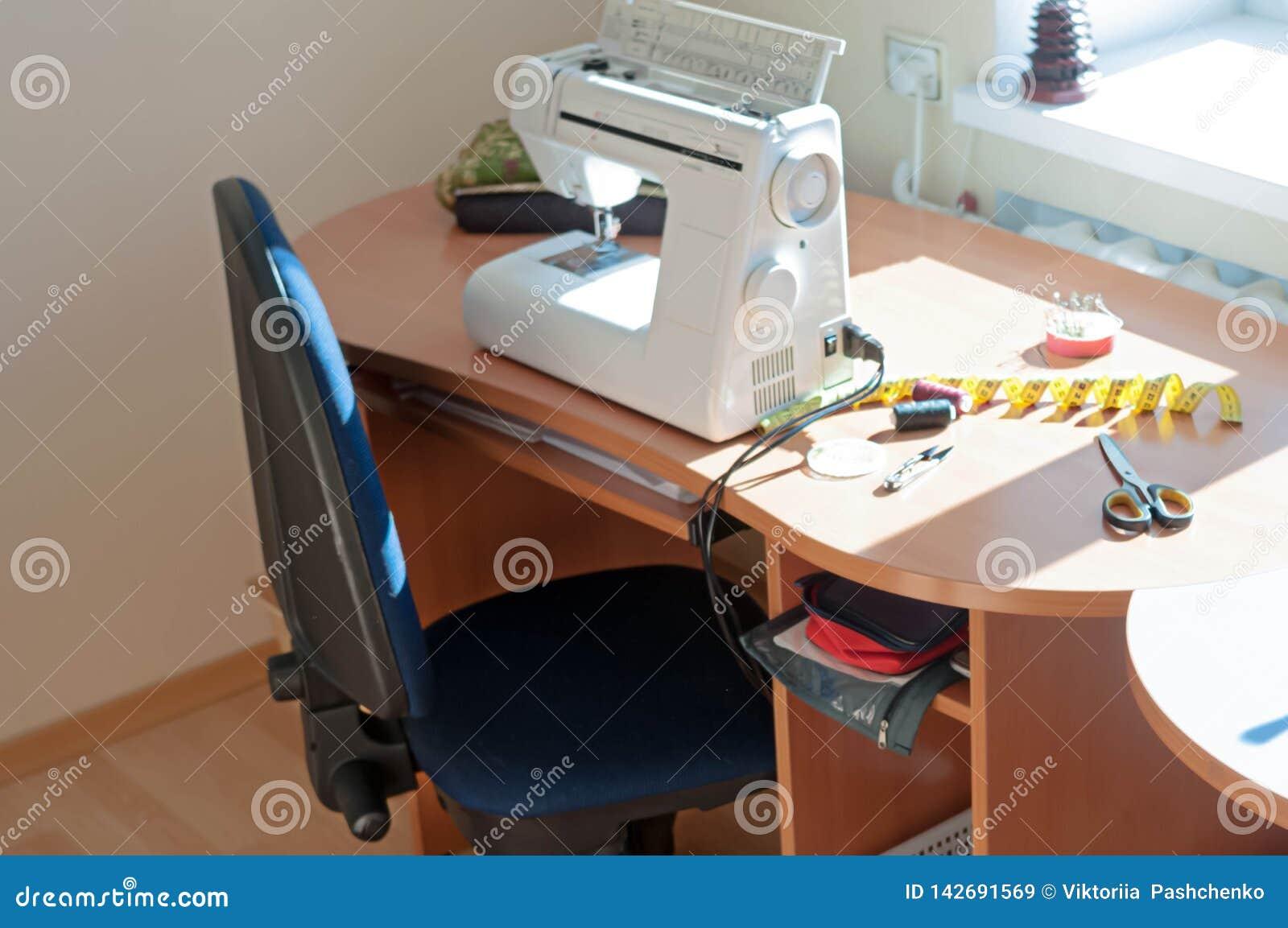 Symaskin som mäter bandet, rullar av tråden och sax på trätabellen med solljus