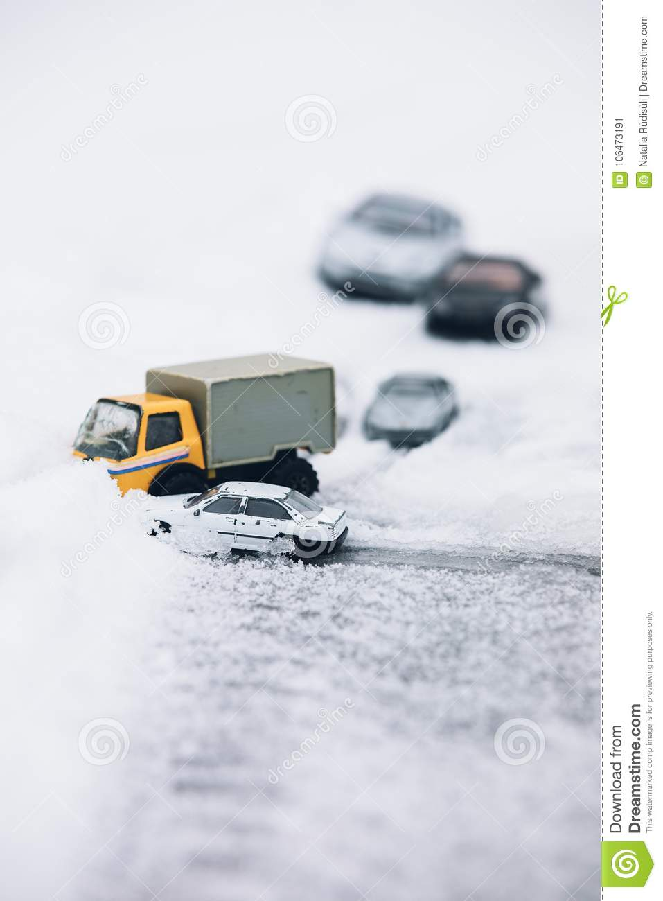 Symbolic car accident in winter on snow road staged with toy car