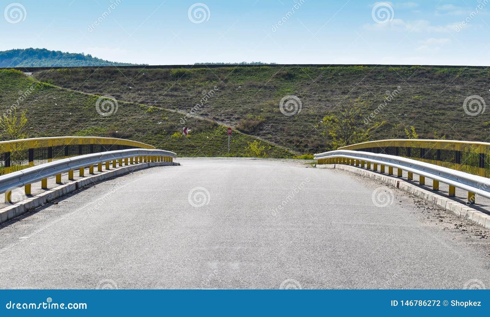 Symmetrisk bild längs den tomma bron på asfaltvägen