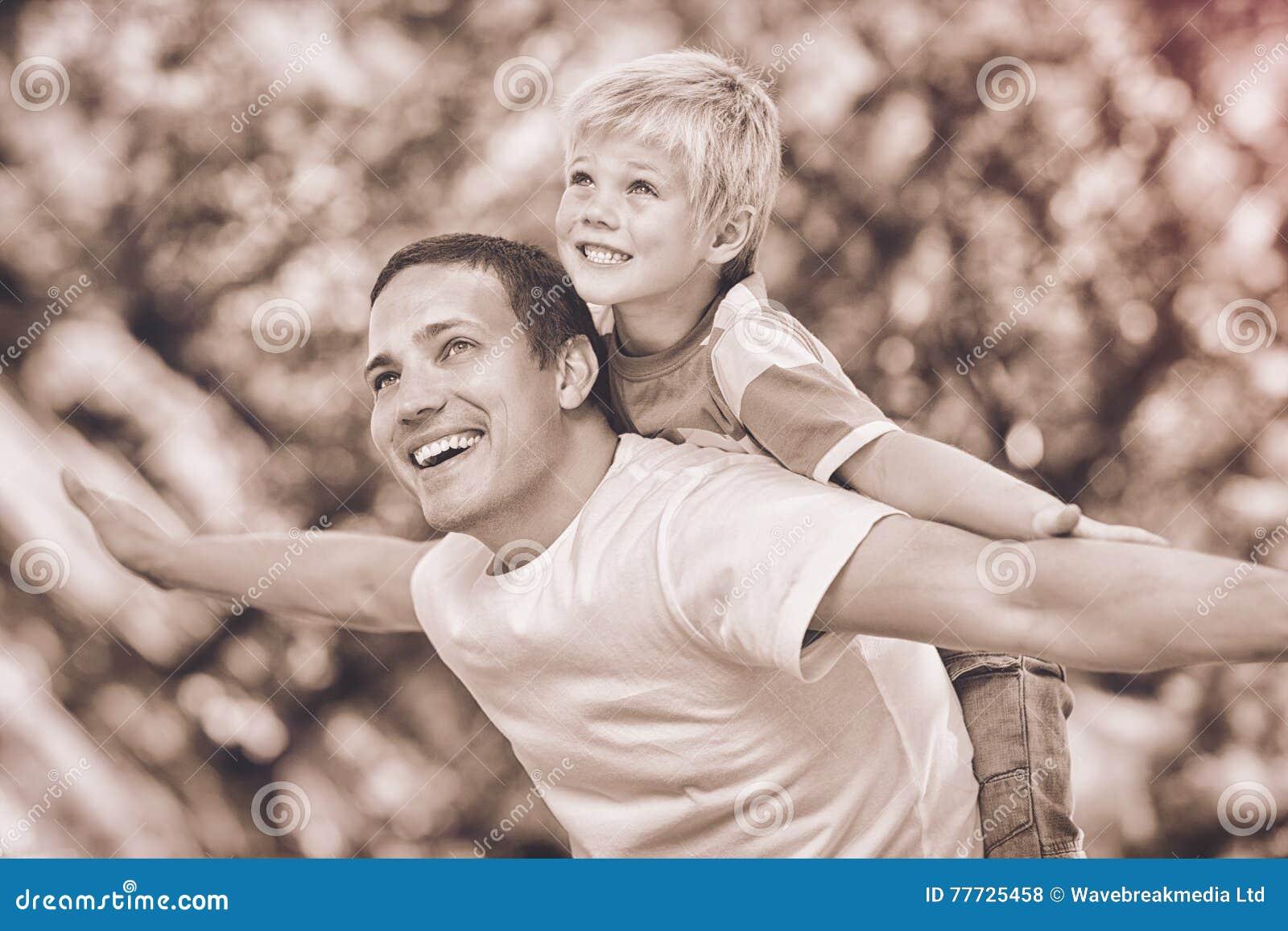 Syn bawić się z jego ojcem w parku podczas lata