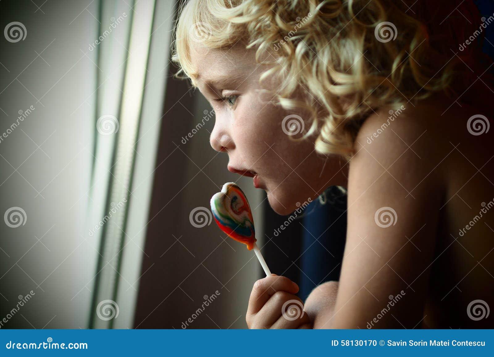 Synade blonda blått behandla som ett barn flickan med en godis i hennes hand som ut ser fönstret