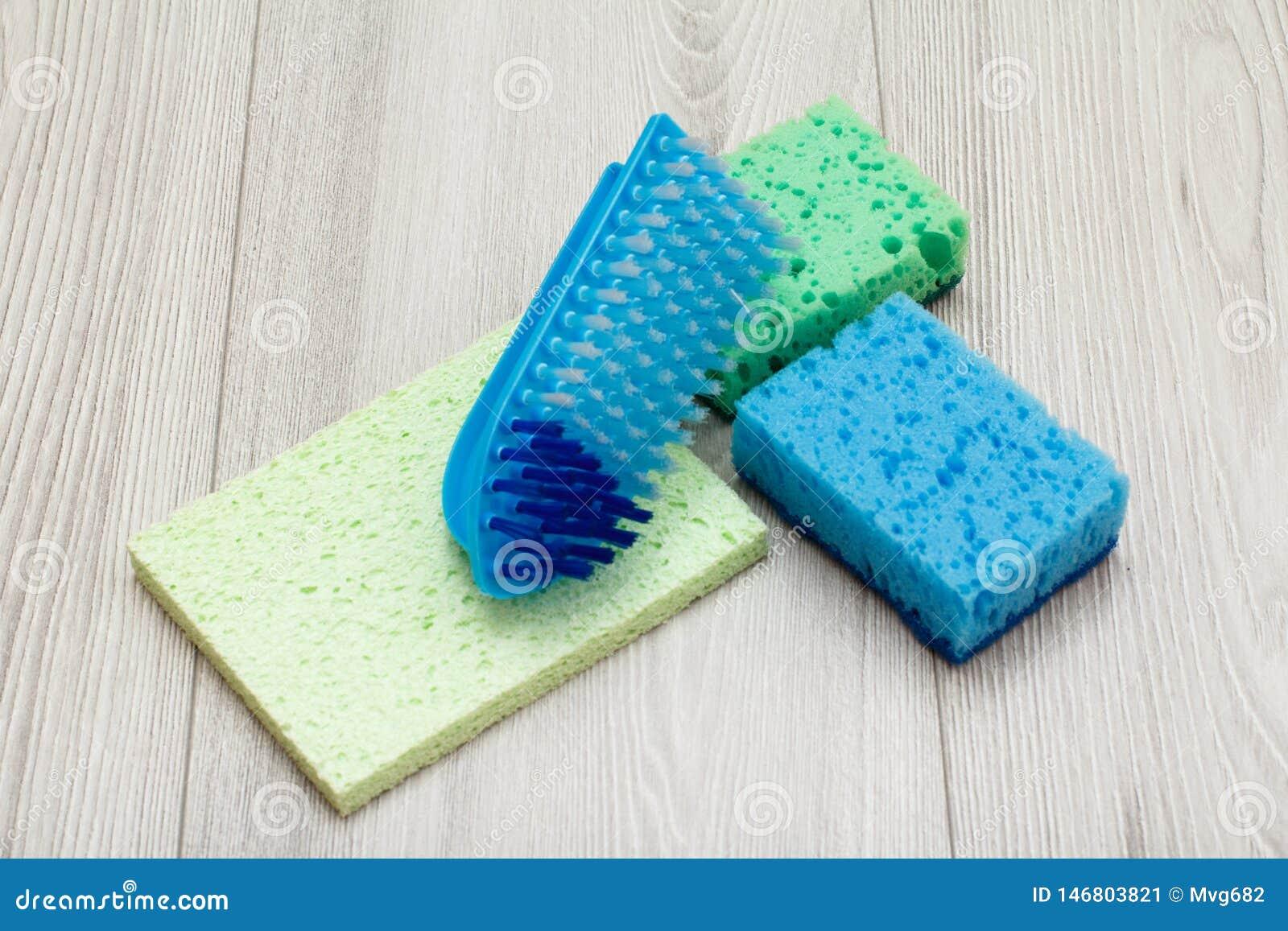 Synthetische sponsen, microfiber servet en borstel voor het schoonmaken op houten raad