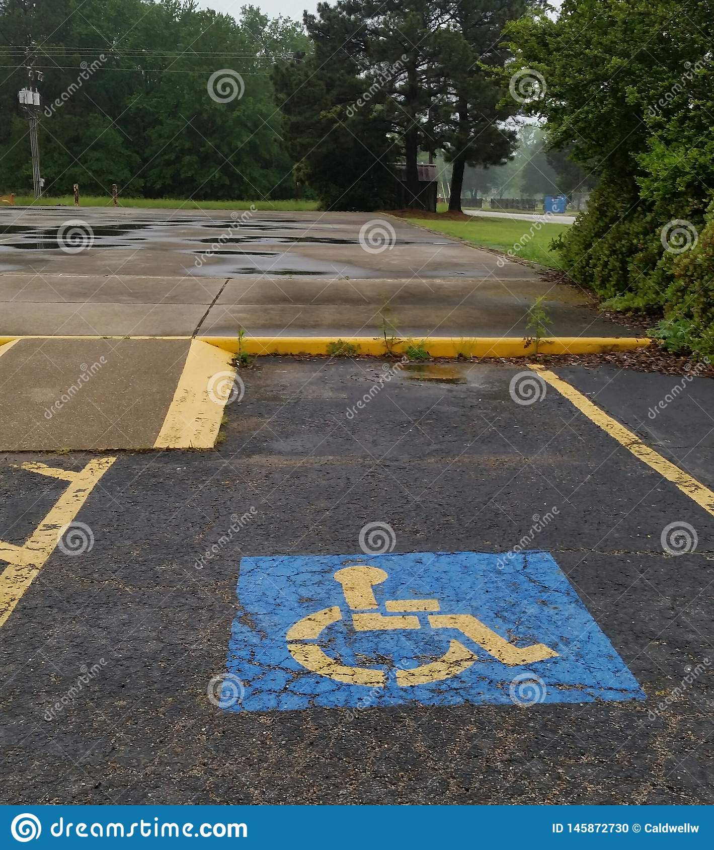 Handicap Parking Space With Ramp. This is an International Handicap Parking symbol painted on a paved parking lot With A Concrete Ramp for a wheel chair stock photo