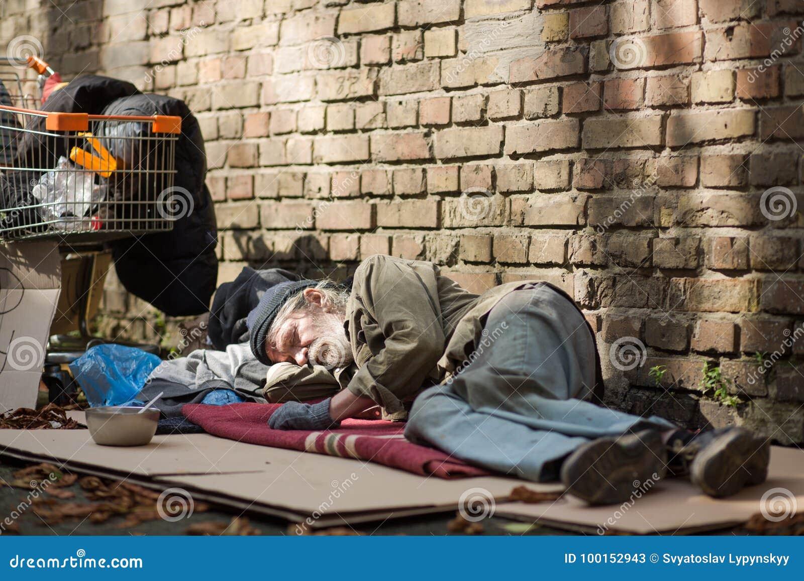 Sypialny bezdomny mężczyzna lying on the beach na kartonie