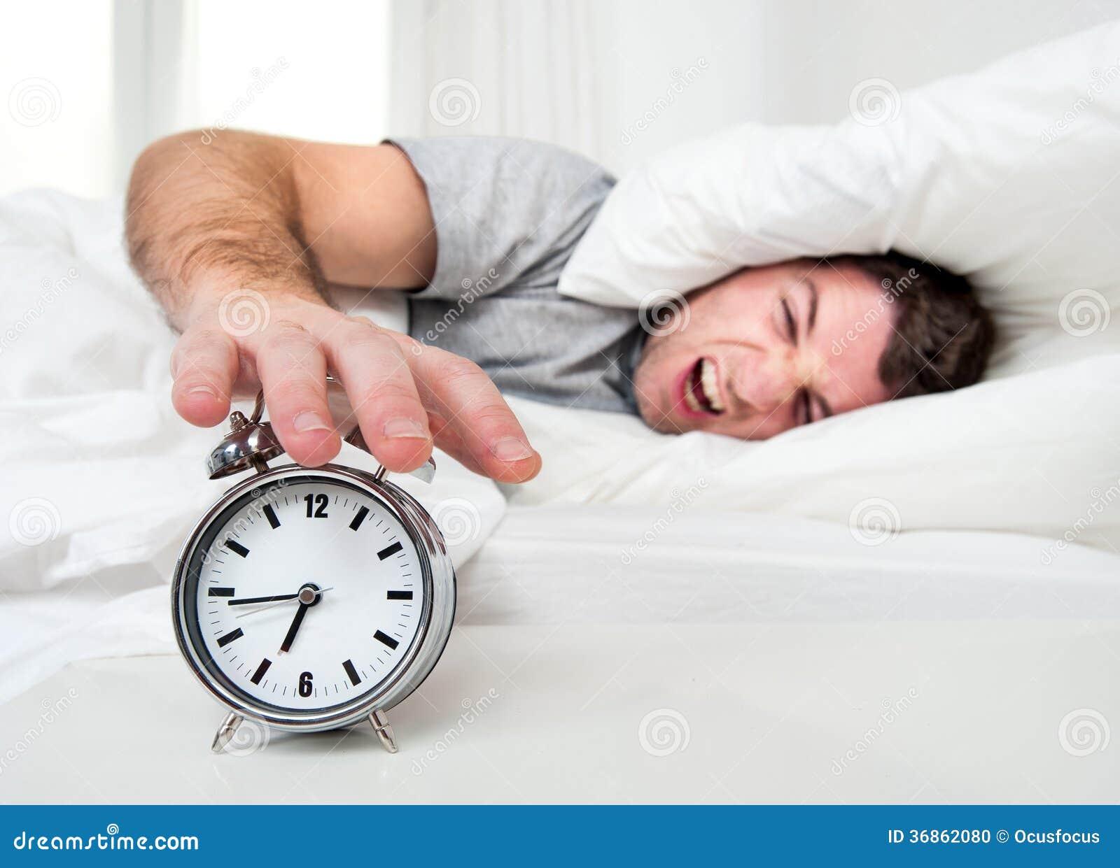 Sypialny mężczyzna zakłócający budzika wczesnym mornin
