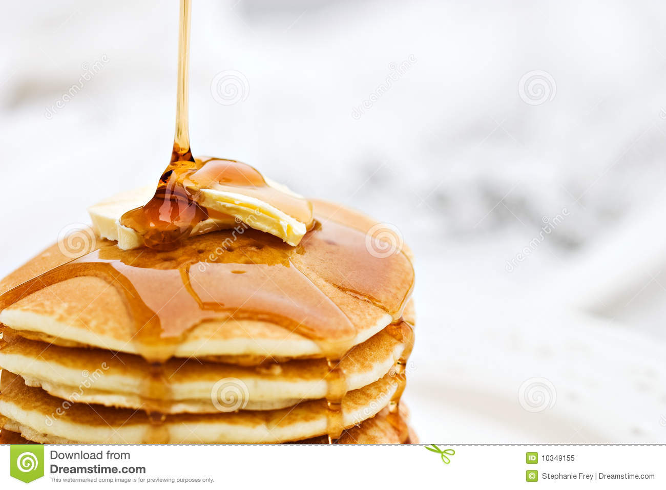 Maple syrup pouring onto pancakes. Shallow DOF with focus on syrup and ...