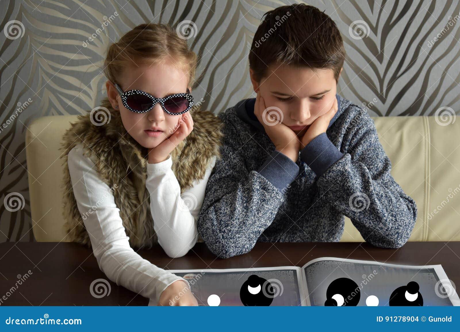 Syskon som ser en tidning