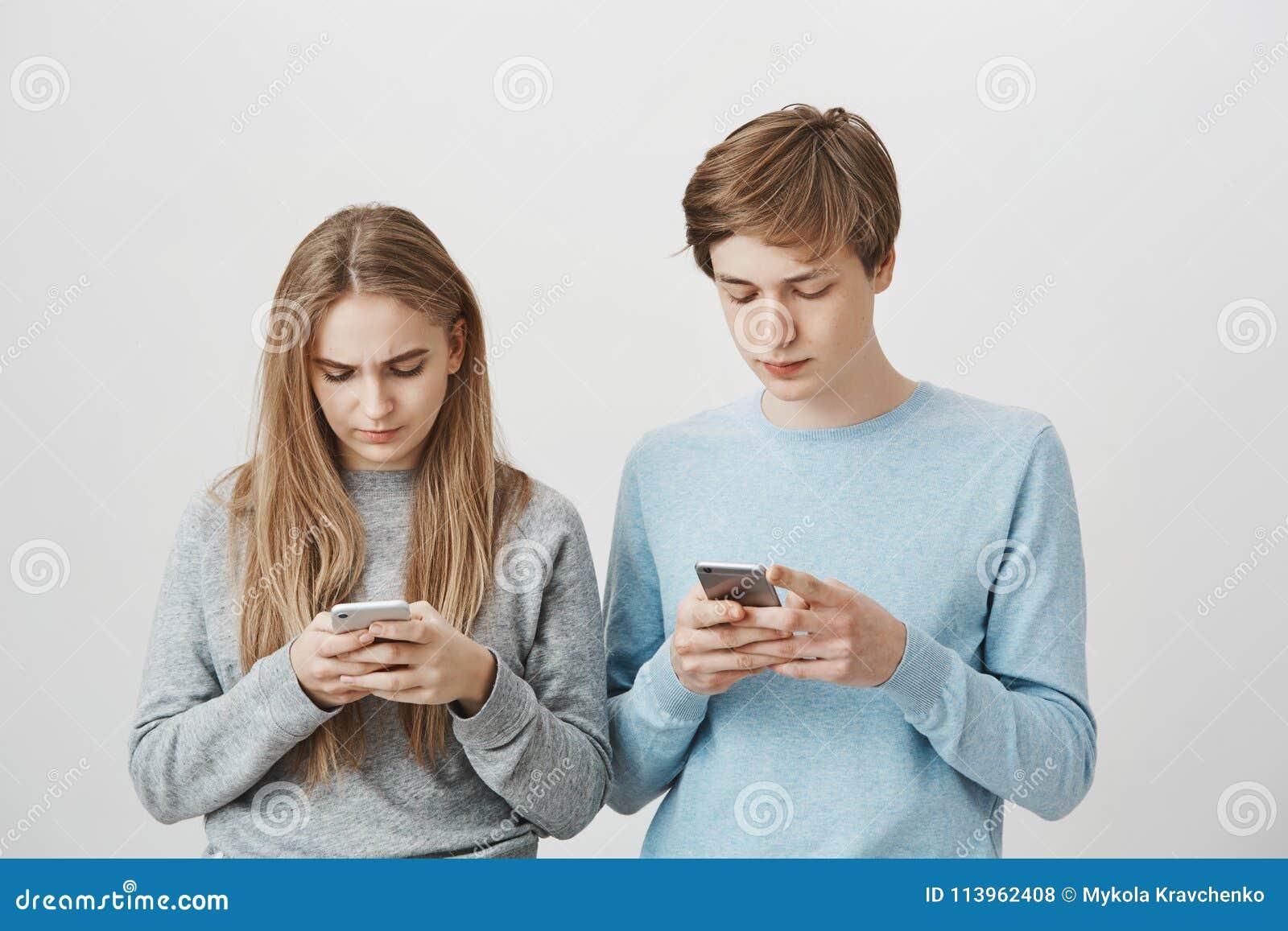Syskon som spelar leken på smartphones som utmanar med de Studioskott av den fokuserade snygga kvinnan och mannen