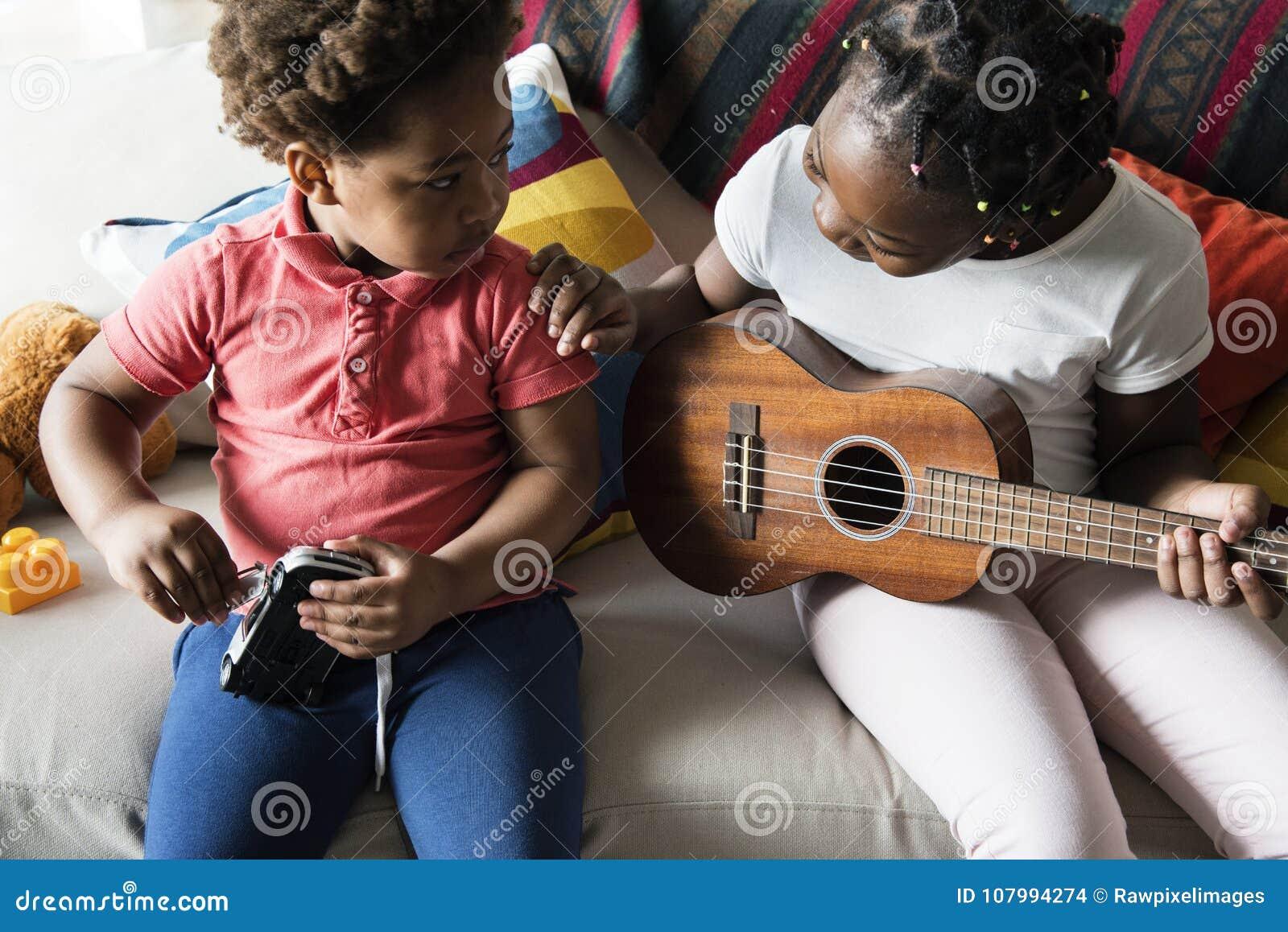 Syskon som spenderar tid som spelar tillsammans gitarren