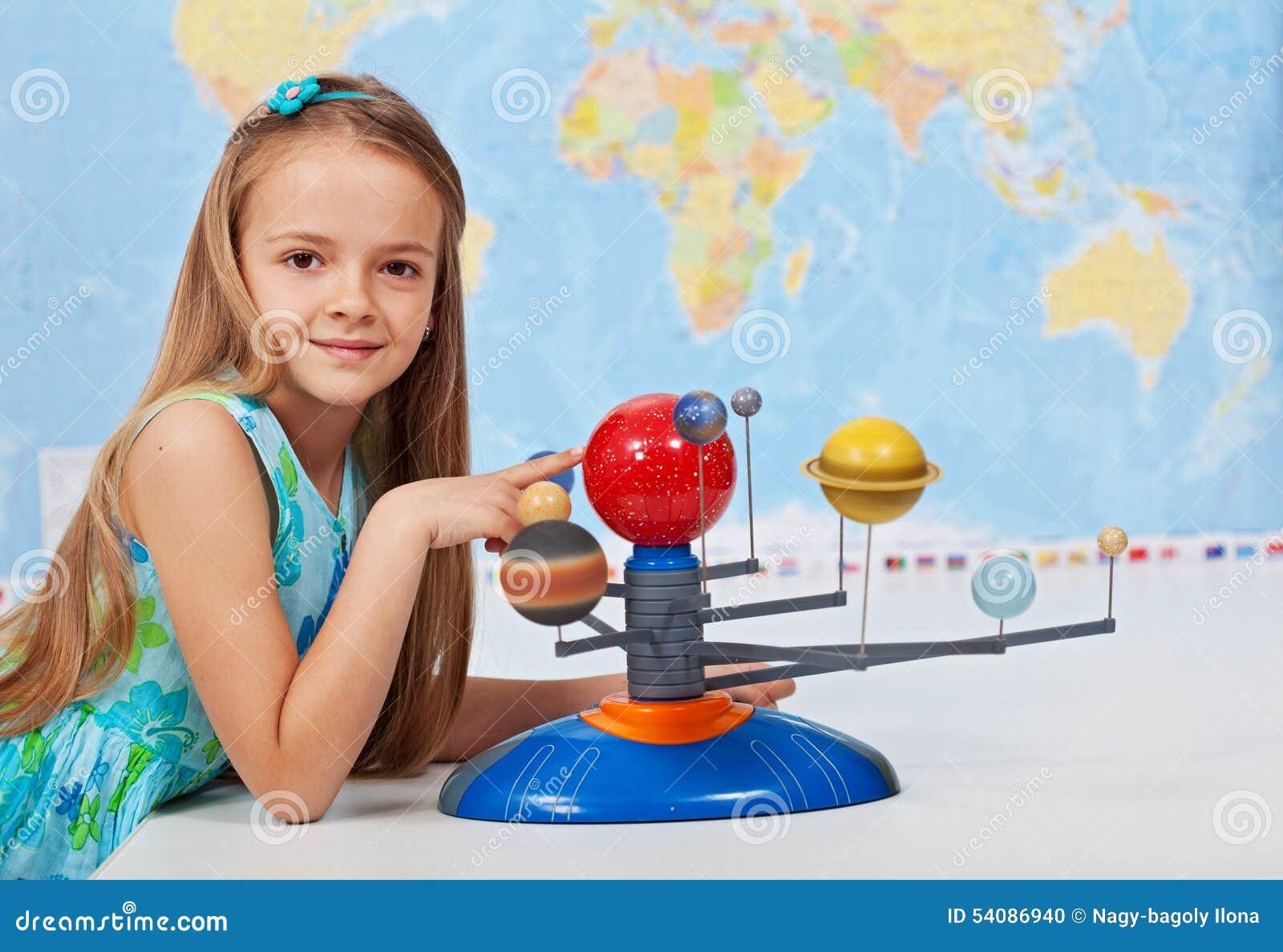 Système solaire d étude de jeune fille dans la classe de la science