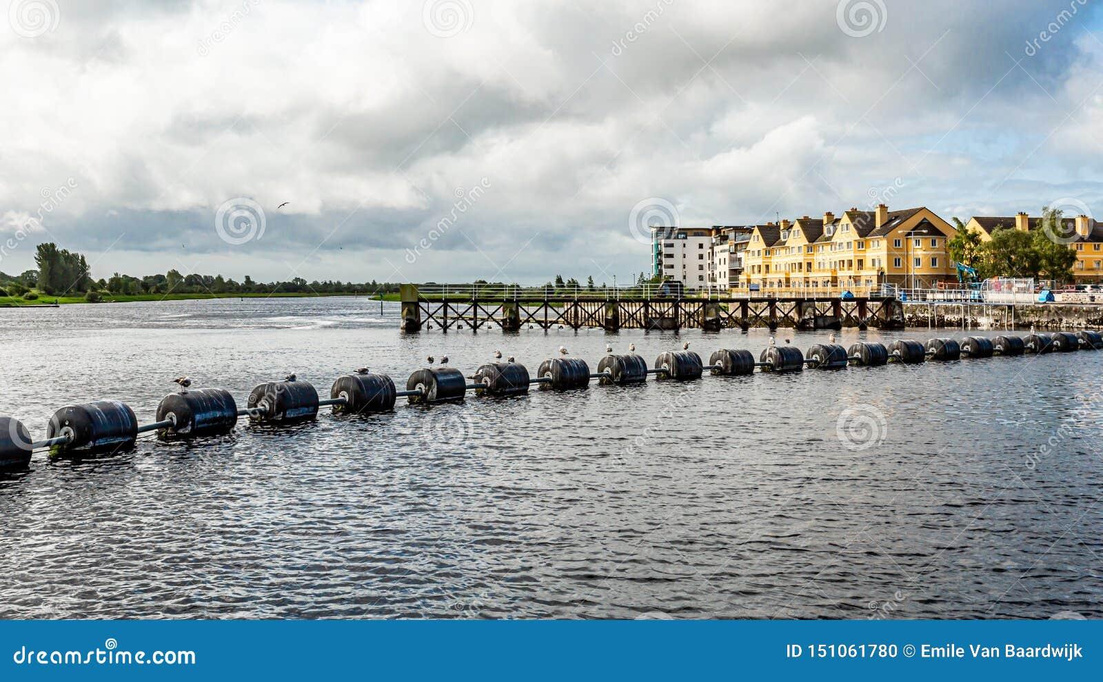 Systeem van slot, waterkering en sluisdeuren in de Shannon-rivier met zwarte boeien in Athlone-stad