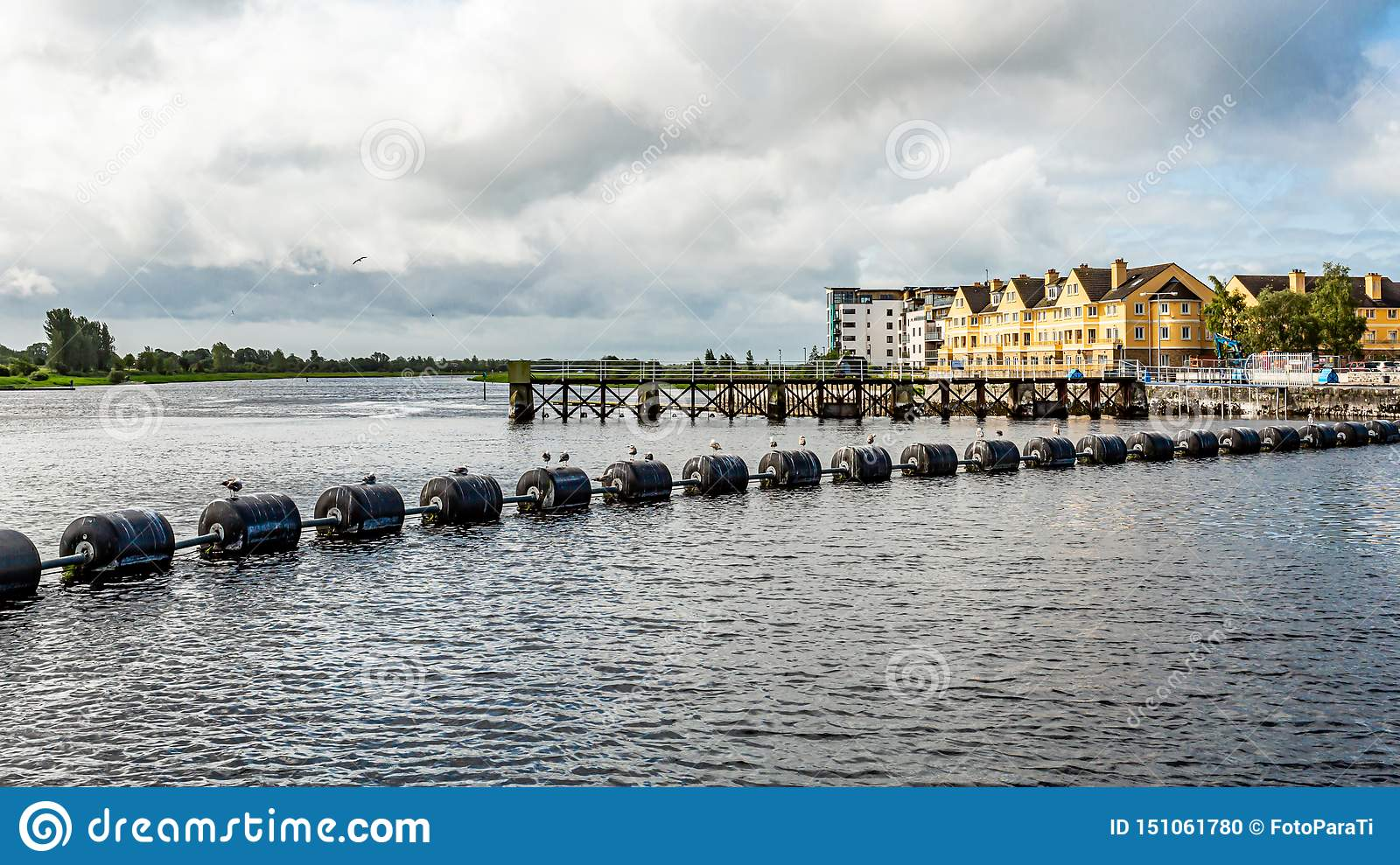 System of lock, weir and sluice gates in the Shannon river with black buoys in Athlone town
