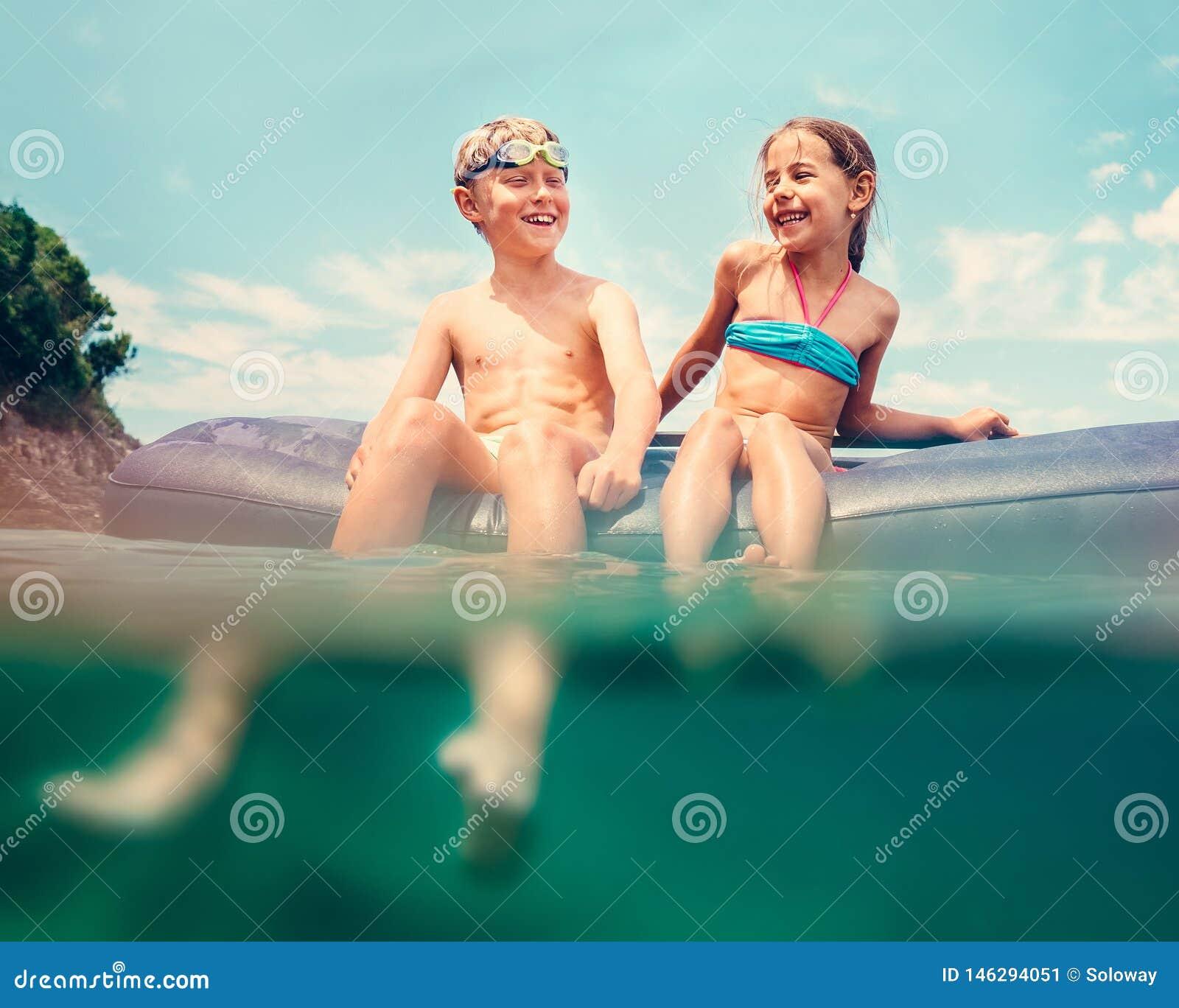 Syster och broder som sitter p? den uppbl?sbara madrassen och tycker om havsvattnet som skrattar glatt n?r bad i havet of?rsiktig