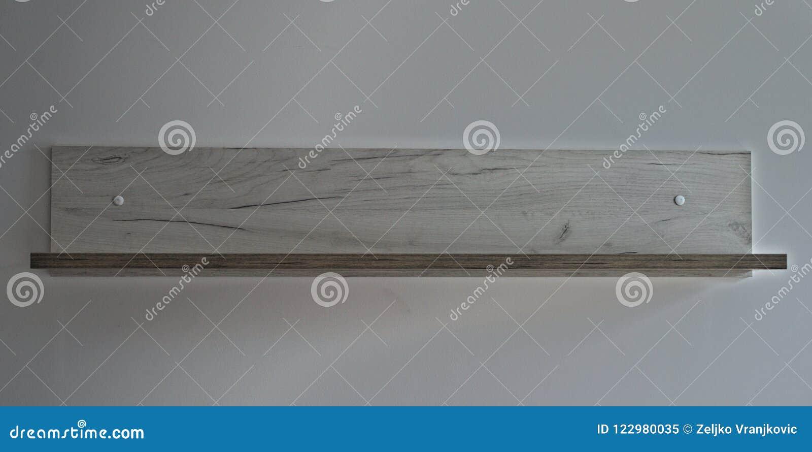Szara drewniana półka na biel ścianie, frontowy widok