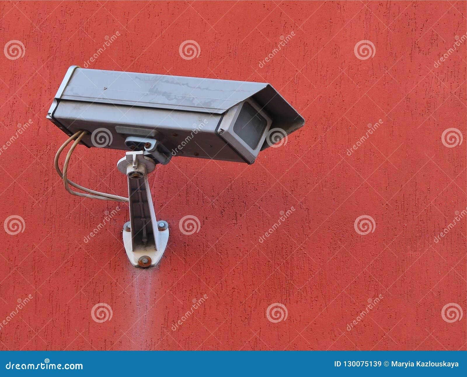 Szara uliczna kamera zewnętrznie nadzór na terakotowej barwionej budynek ścianie