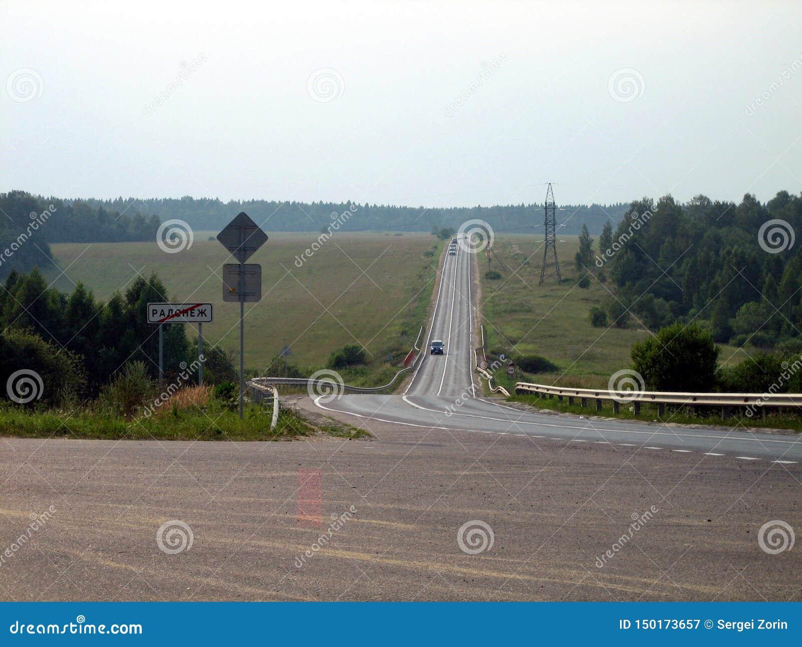 Szary faborek droga między polami i lasami na chmurnym dniu