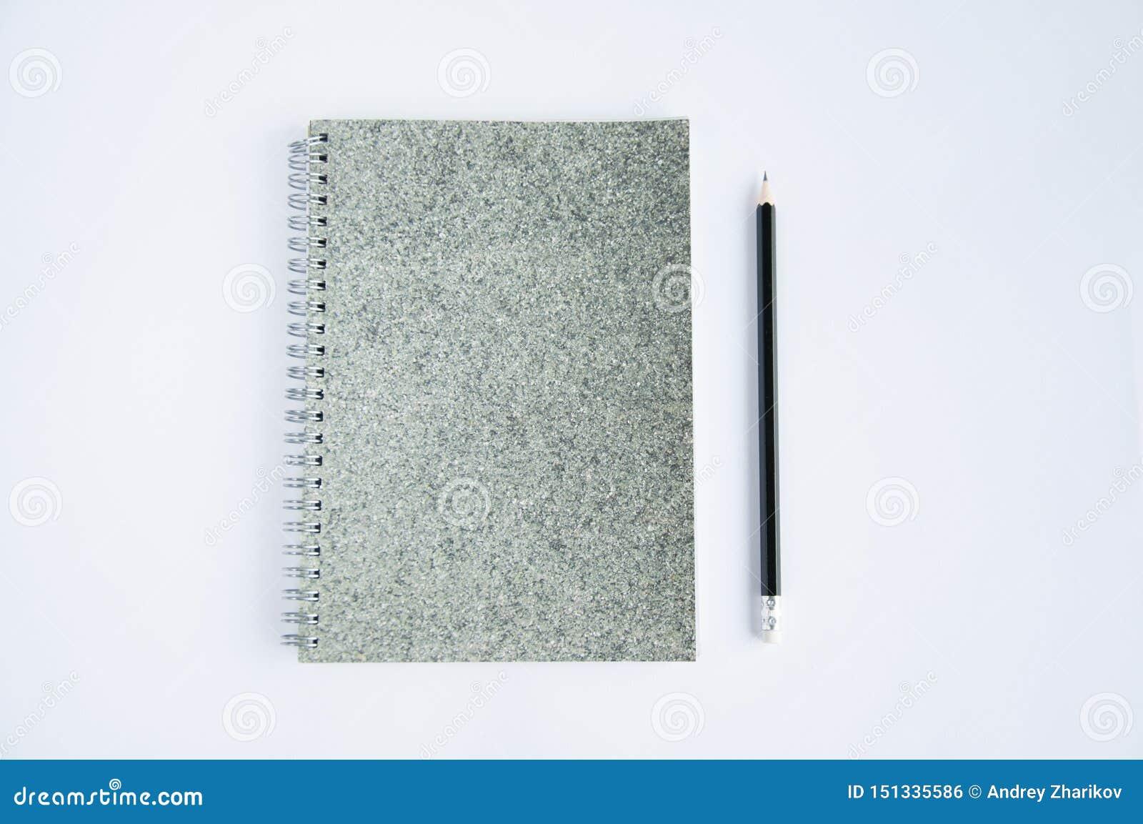 Szary notatnik kłama na stole Na ochraniaczu lub pobliski ja jest czarnym ołówkiem