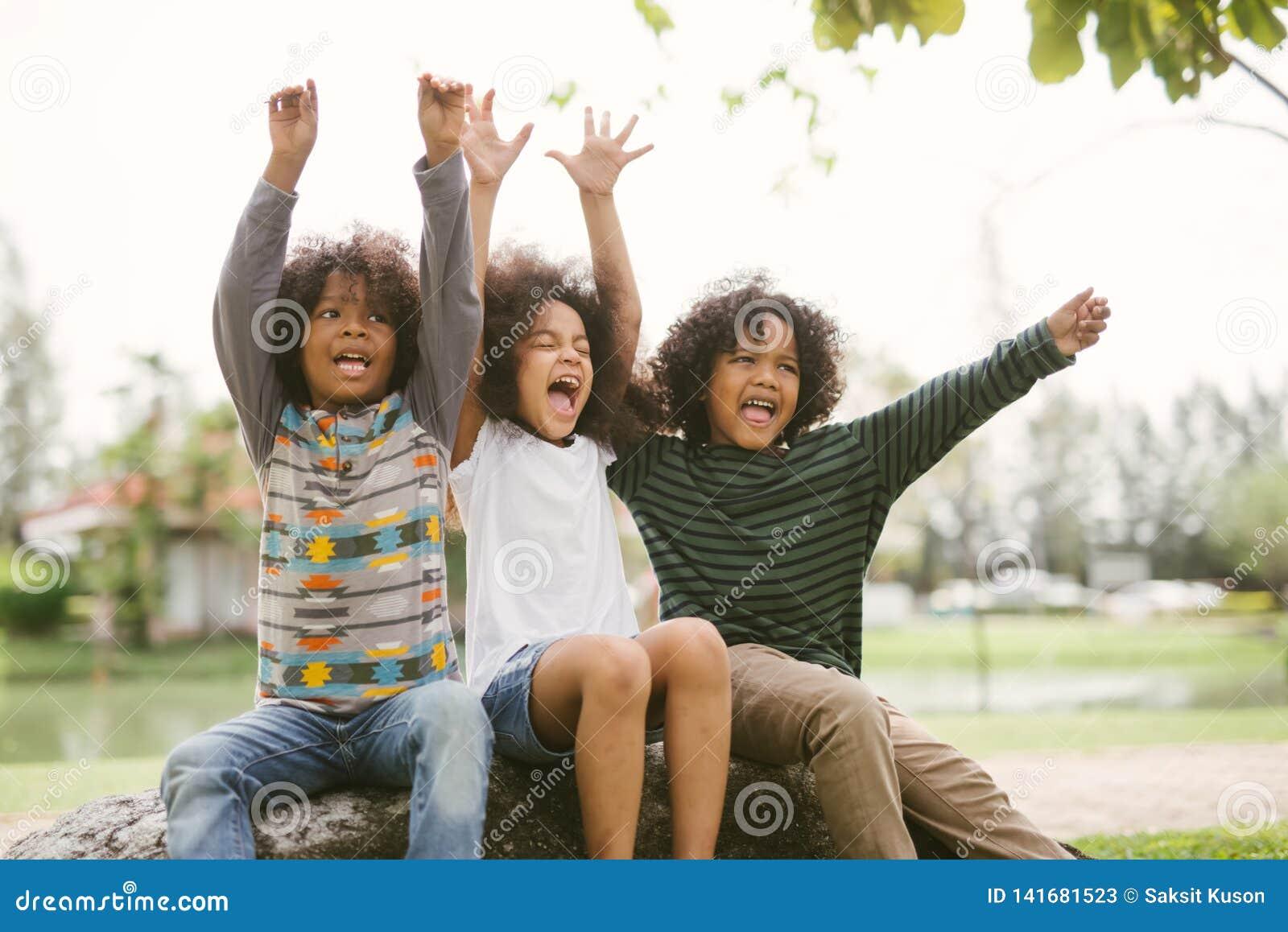 Szczęśliwa amerykanin afrykańskiego pochodzenia chłopiec żartuje dzieci joyfully rozochoconych i roześmianych Pojęcie szczęście