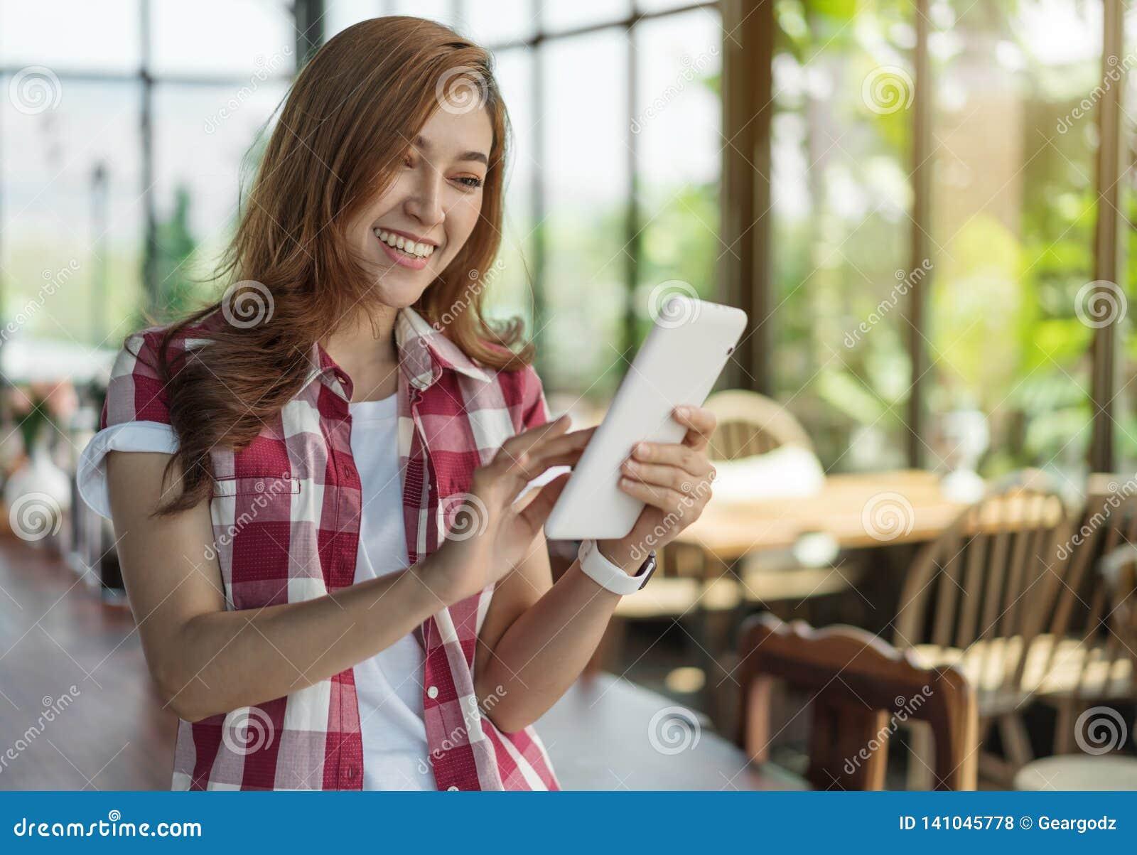 Szczęśliwa kobieta używa cyfrową pastylkę w kawiarni