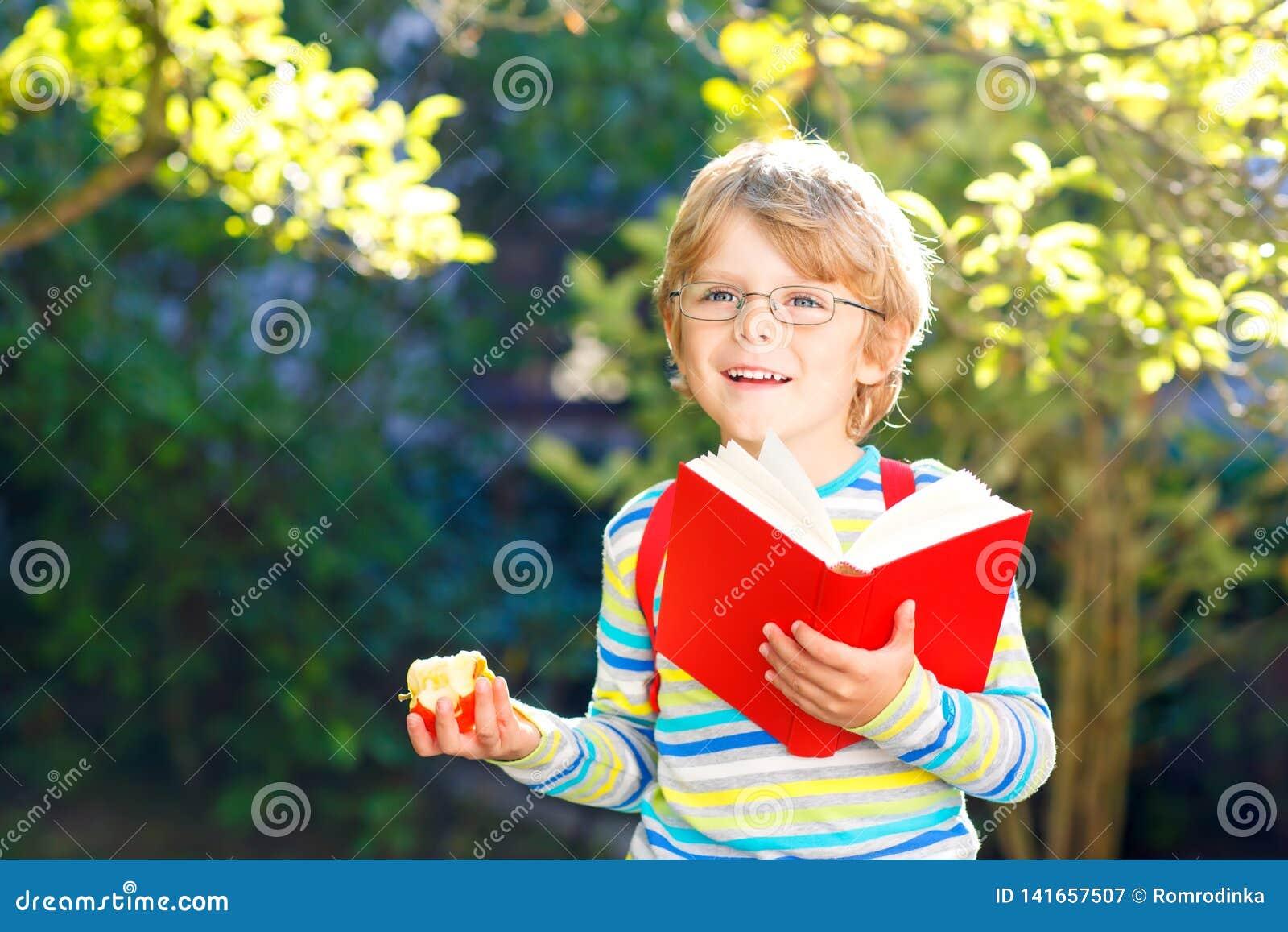 Szczęśliwa mała preschool dzieciaka chłopiec z szkłami, książkami, jabłkiem i plecakiem na jego pierwszy dniu, szkoła lub pepinie