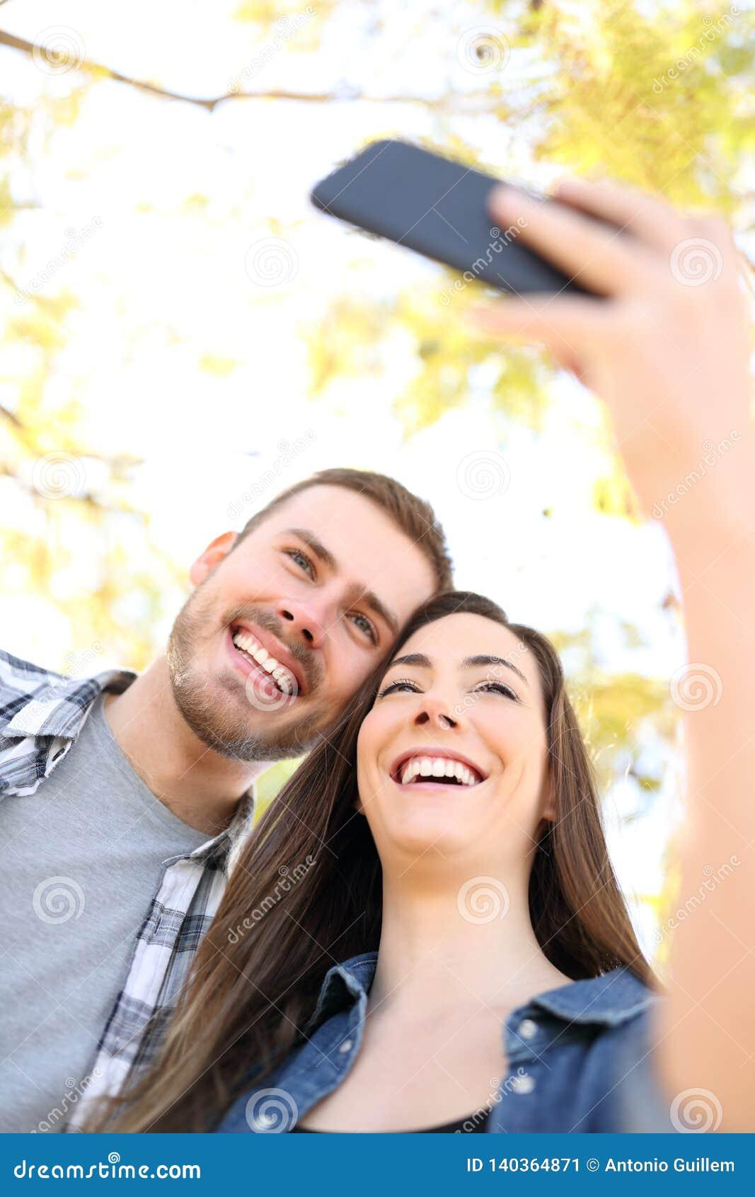 Szczęśliwa para bierze selfies z smartphone