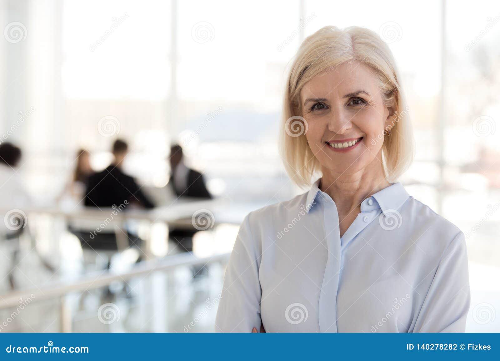 Szczęśliwa pomyślna starzejąca się biznesowa dama pozuje patrzejący kamerę