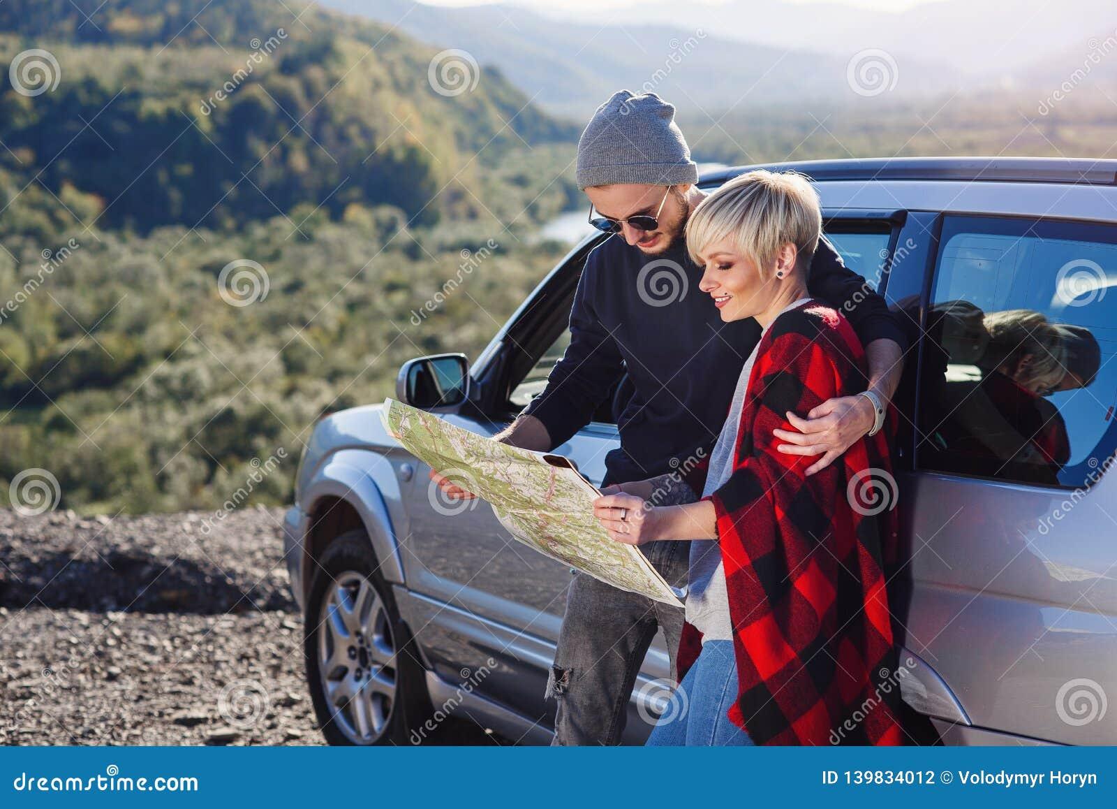Szczęśliwa turystyczna para z papierowej mapy pobliskim dzierżawiącym samochodem Modni młodzi ludzie używa mapę Podróżować samoch