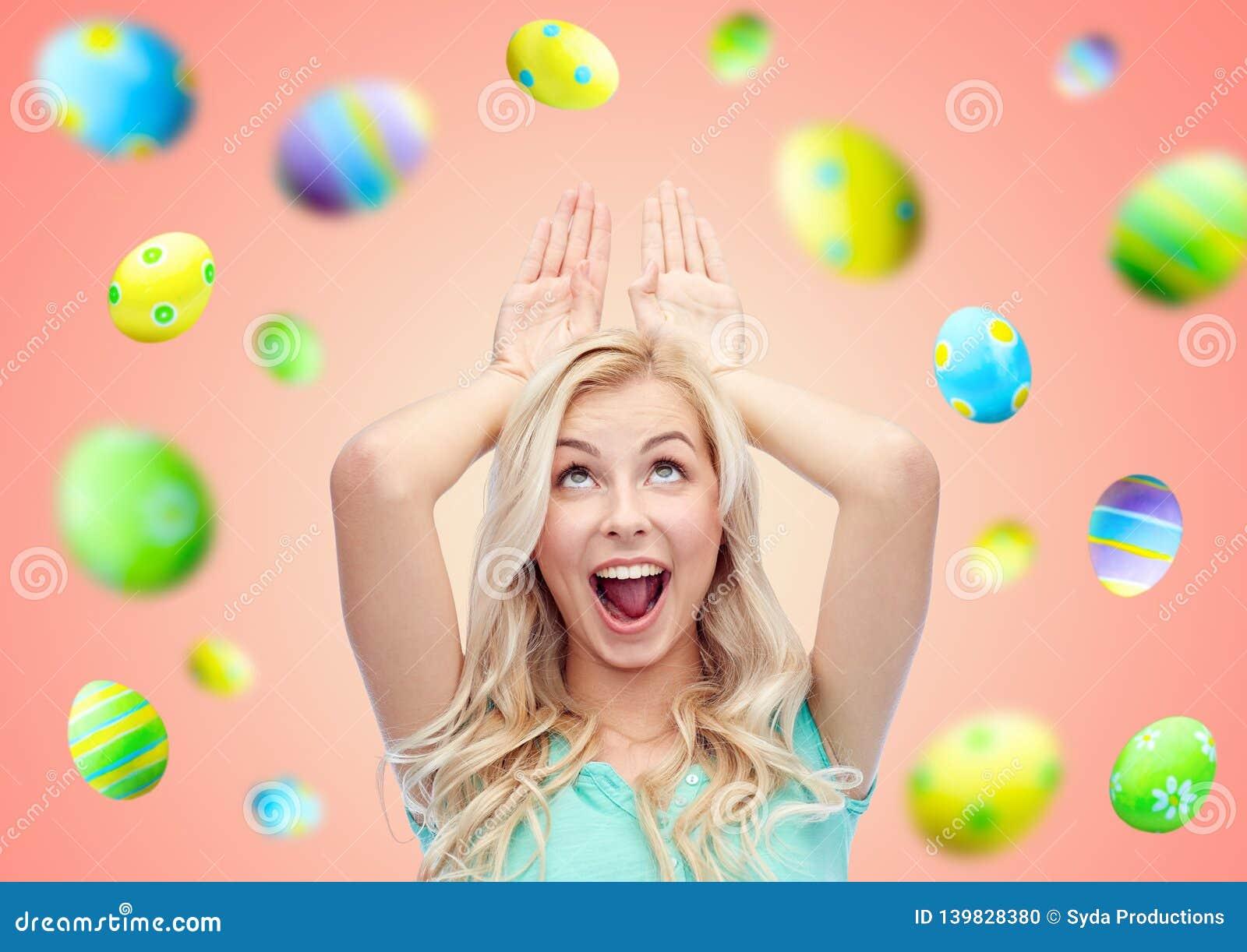 Szczęśliwa uśmiechnięta młoda kobieta robi Easter królika ucho