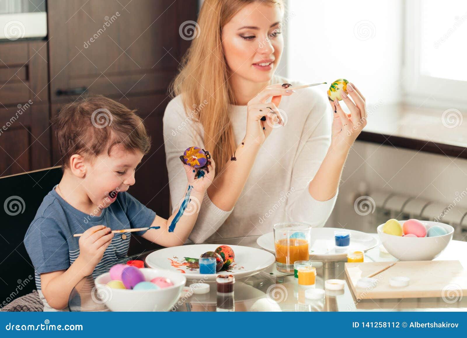Szczęśliwa Wielkanocna potomstwo matka i jej mały syn maluje Wielkanocnych jajka