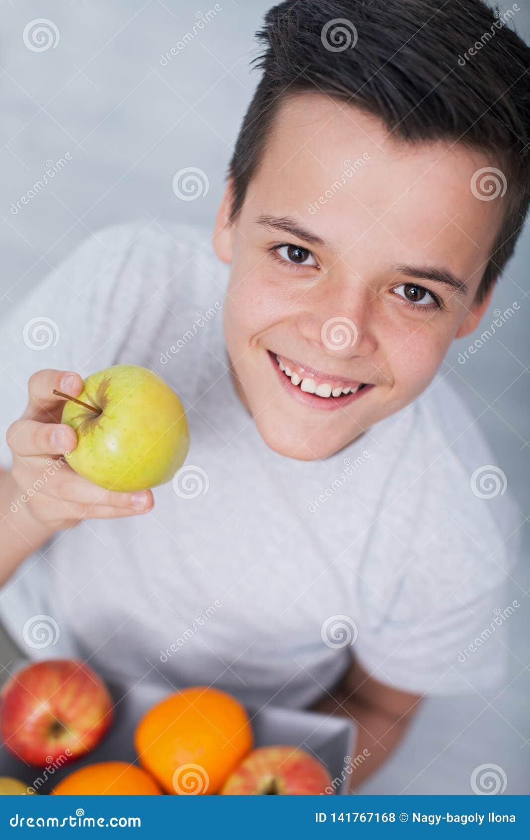 Szczęśliwa zdrowa nastolatek chłopiec z talerzem owoc - trzymać jabłka, przyglądającym w górę