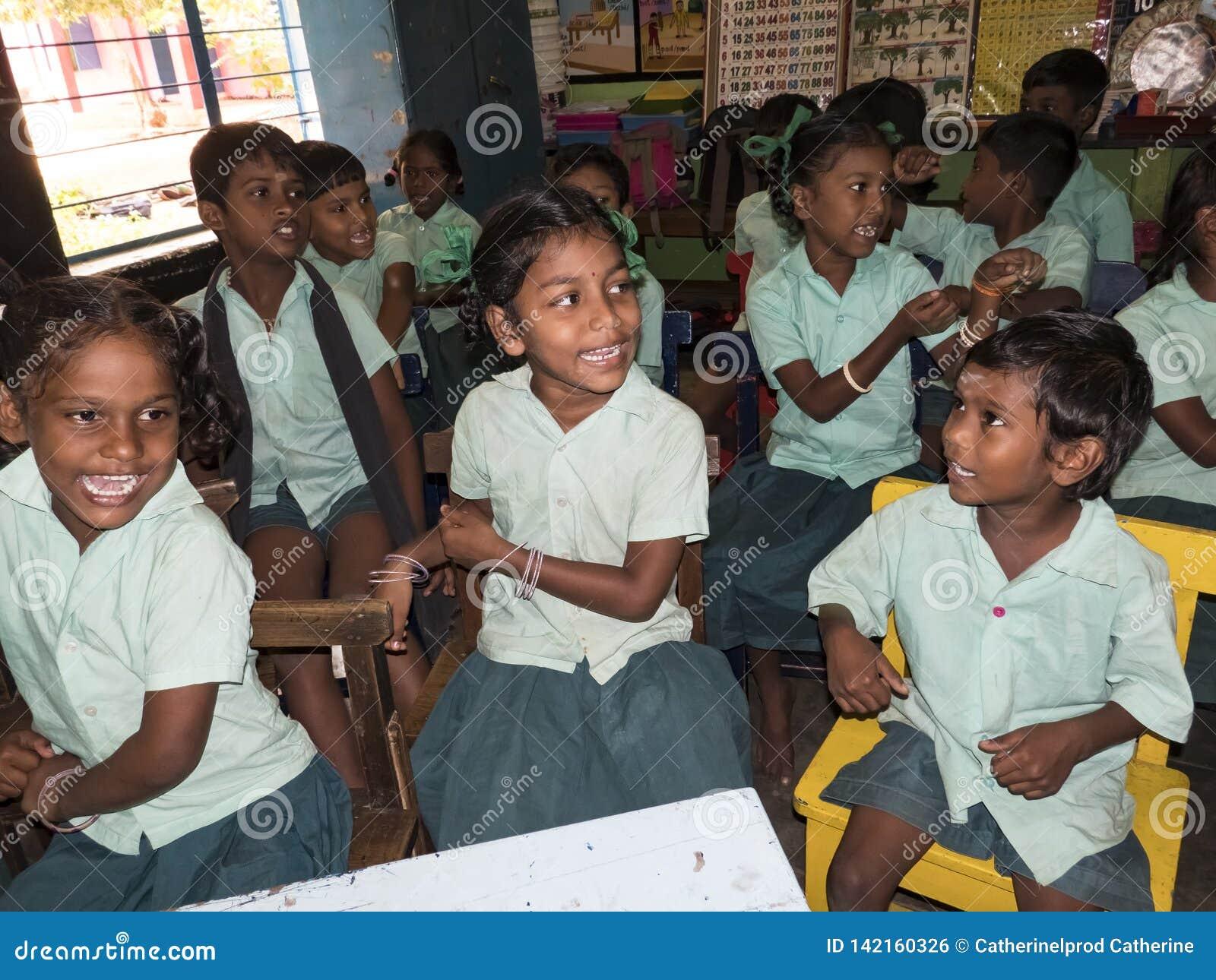 Szczęśliwe śmieszne dziecko przyjaciół dziewczyny i chłopiec koledzy z klasy uśmiecha się śmiać się w sali lekcyjnej przy szkołą