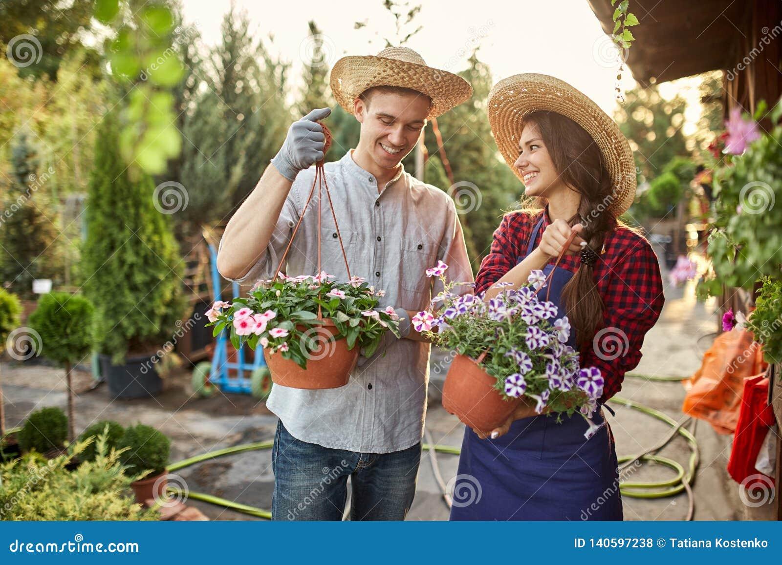 Szczęśliwe faceta i dziewczyny ogrodniczki w słomianych kapeluszy chwycie puszkują z petunią na ogrodowej ścieżce wewnątrz na sło