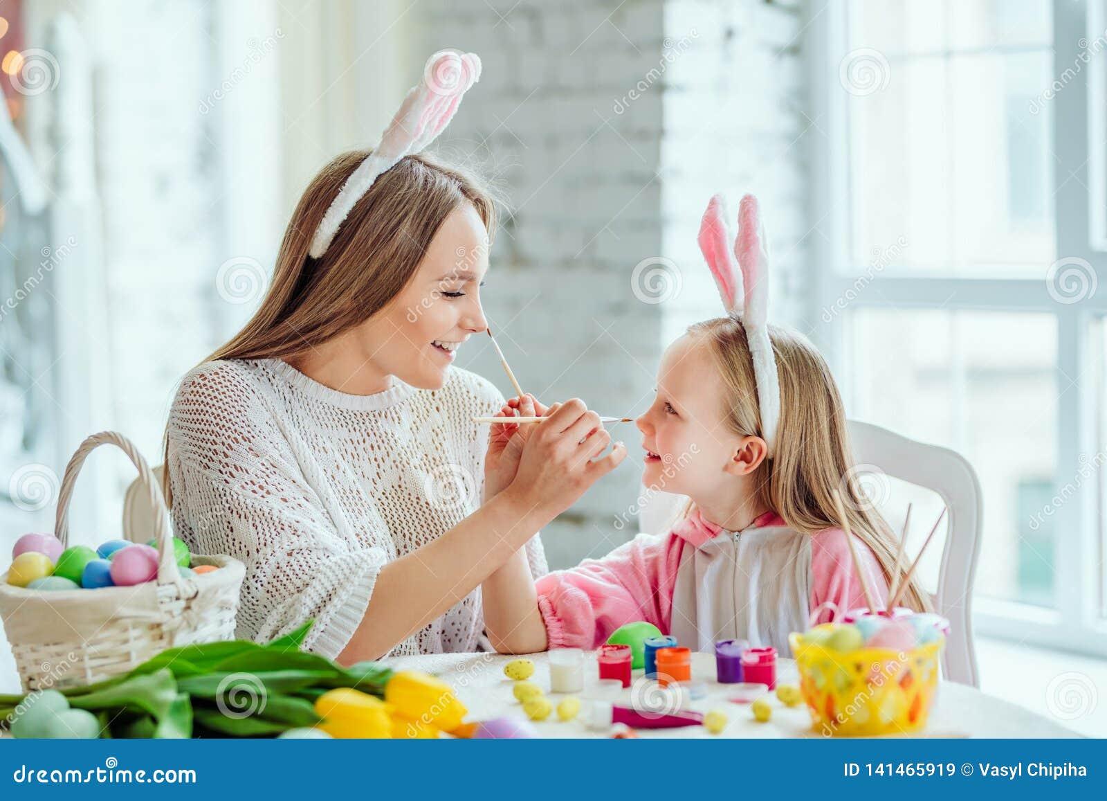 Szczęśliwi Wielkanocni przygotowania Mama i córka przygotowywamy dla wielkanocy wpólnie Na stole jest kosz z Wielkanocnymi jajkam