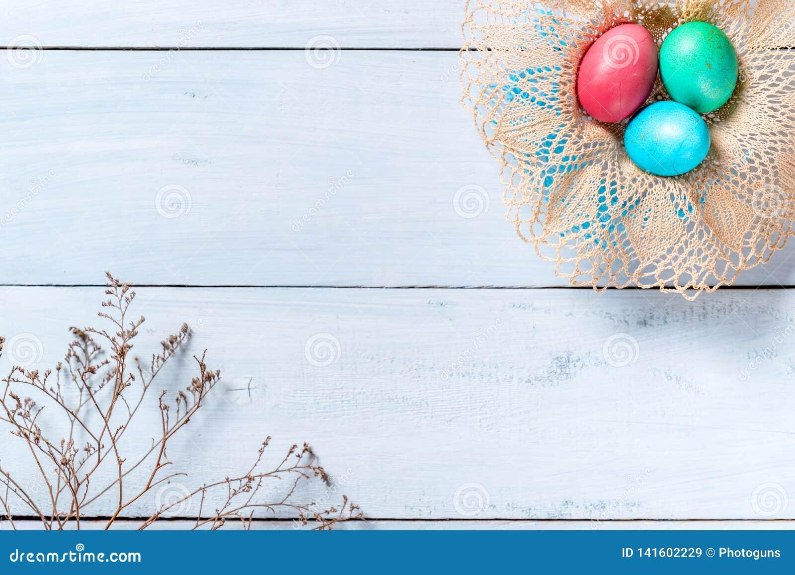 Szczęśliwy Easter granicy tło, rama kolorowi Easter jajka w koszu i gałąź wysuszeni kwiaty,