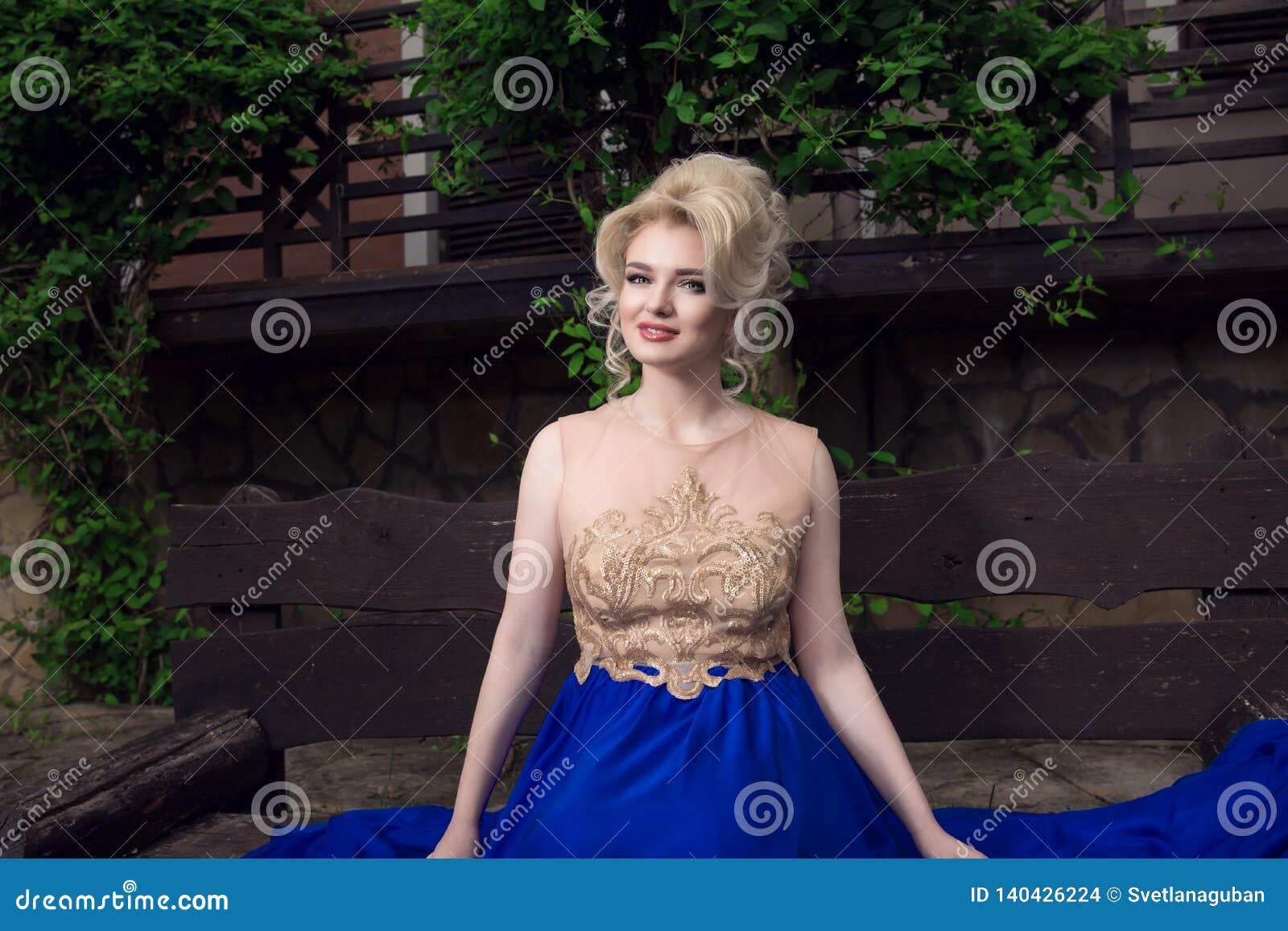 Szczęśliwy, ono uśmiecha się, piękna blondynki kobieta w eleganckiej sukni