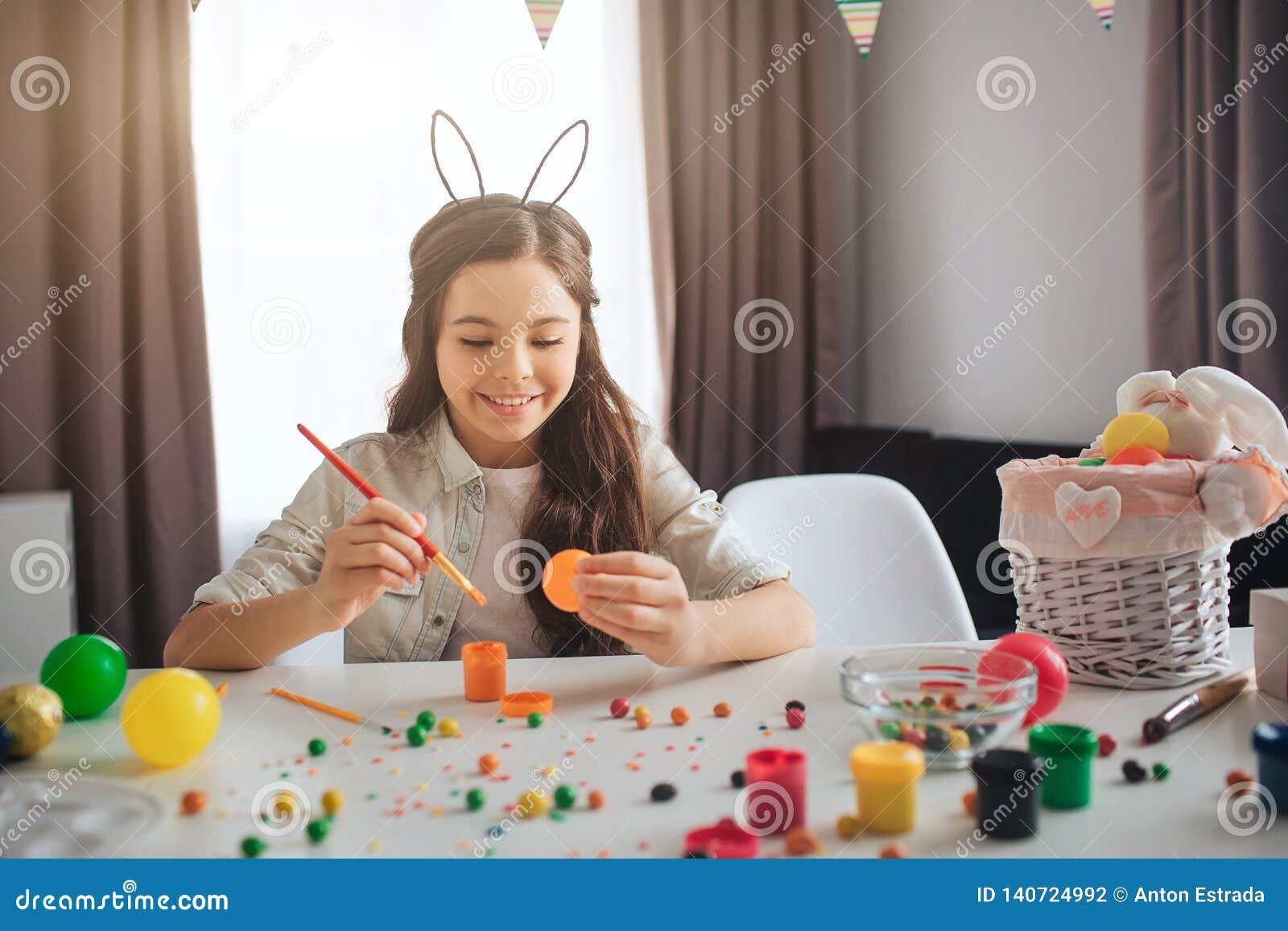 Szczęśliwy pozytywny nastolatka narządzanie dla wielkanocy Siedzi samotnie przy stołu i obrazu jajkami Dziewczyna uśmiech Jest ub