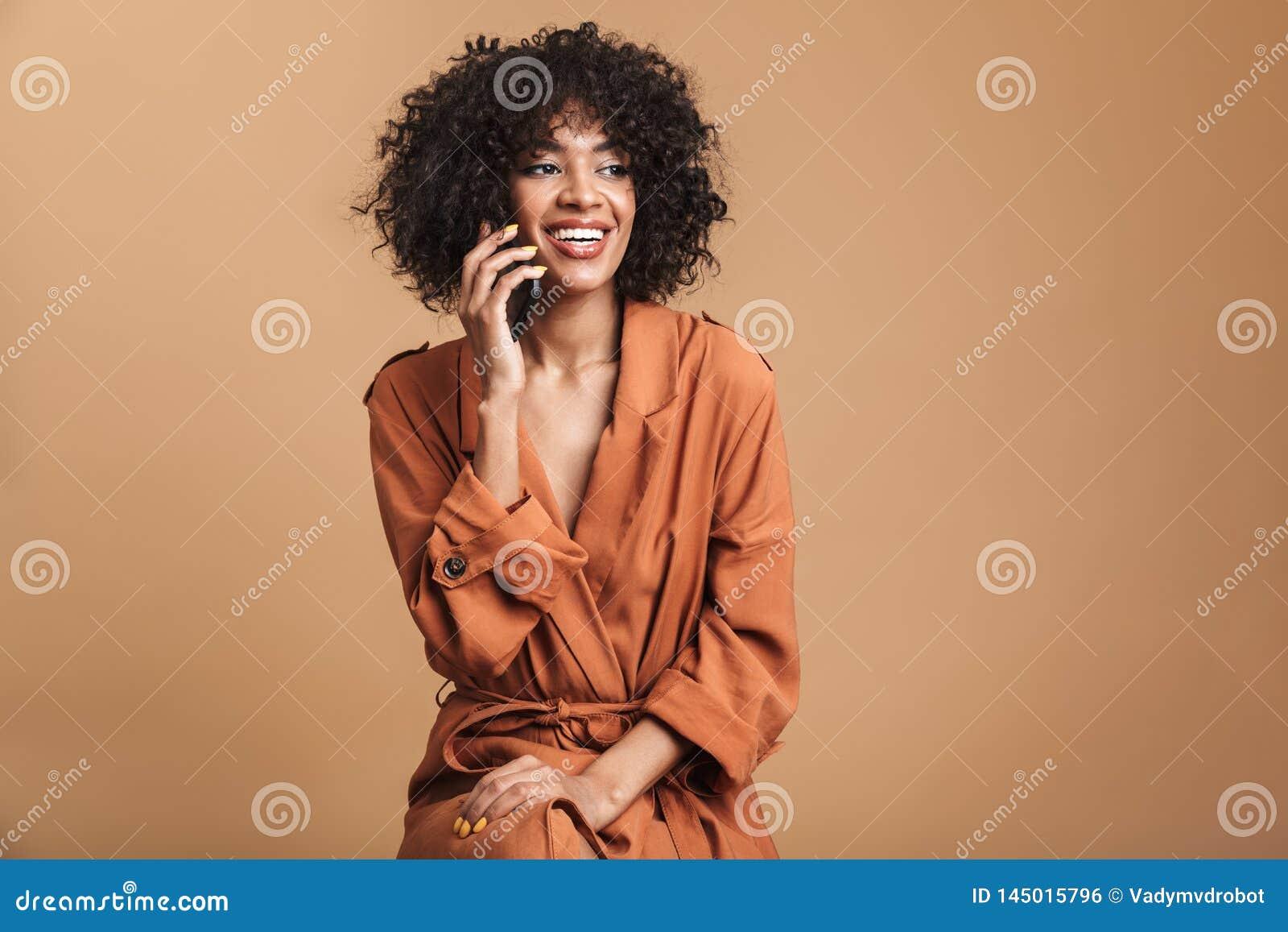 Szcz??liwa ?adna afryka?ska kobieta opowiada smartphone i patrzeje daleko od