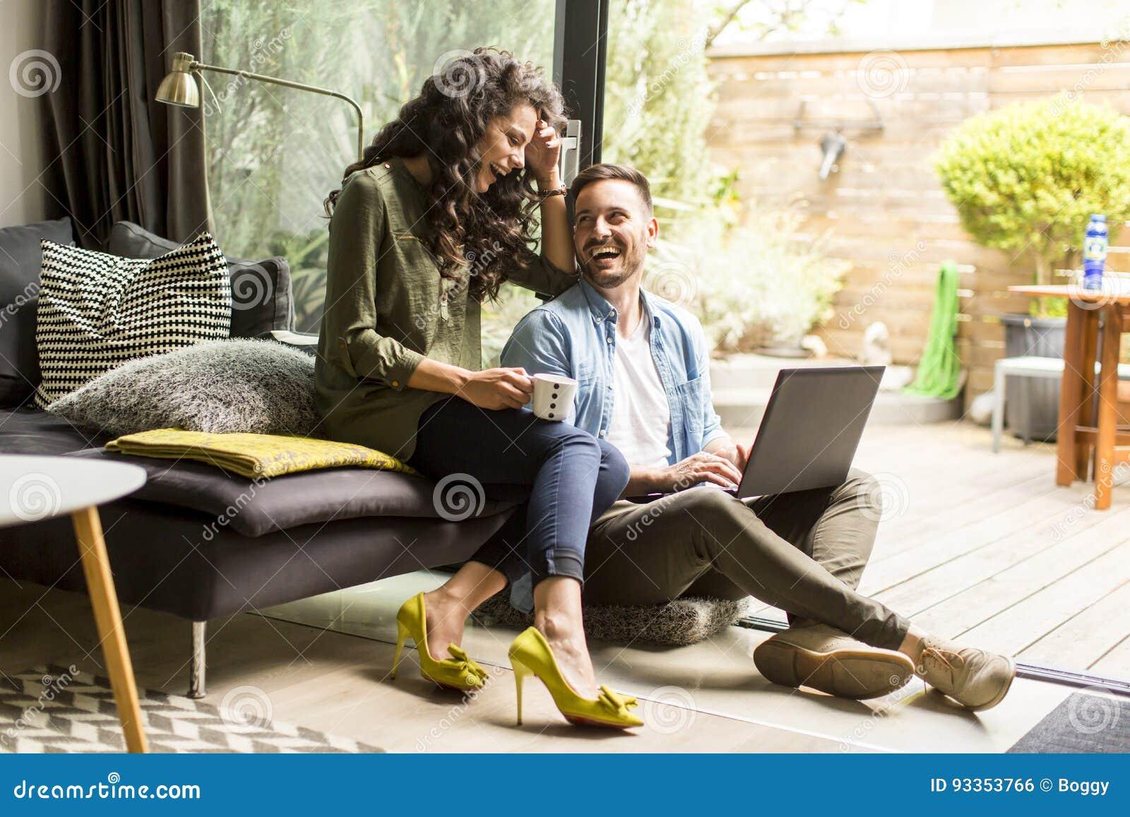 Szczęśliwa śliczna para w miłości pije kawę i smili z laptopem