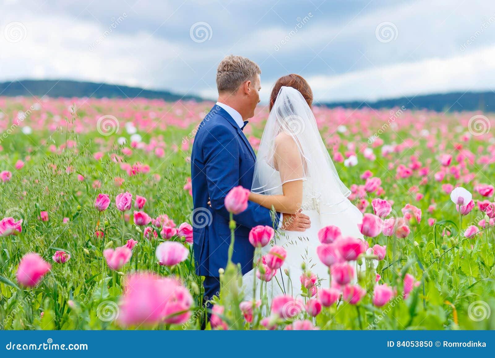 Szczęśliwa ślub para w różowym maczka polu
