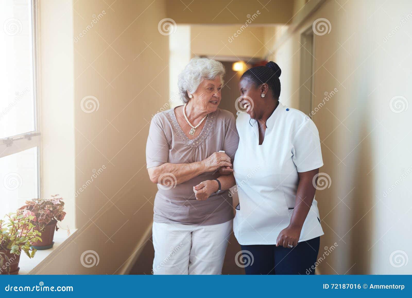 Szczęśliwa żeńska opiekunu i seniora kobieta chodzi wpólnie