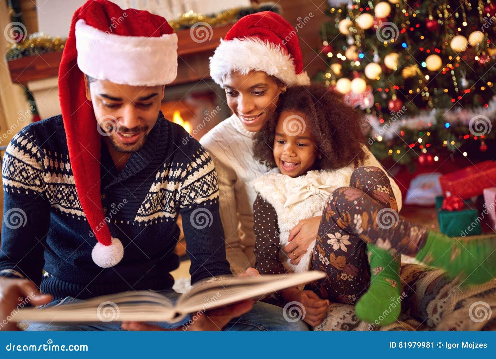 Szczęśliwa afro Amerykańska rodzina czyta książkę przy grabą na bożych narodzeniach