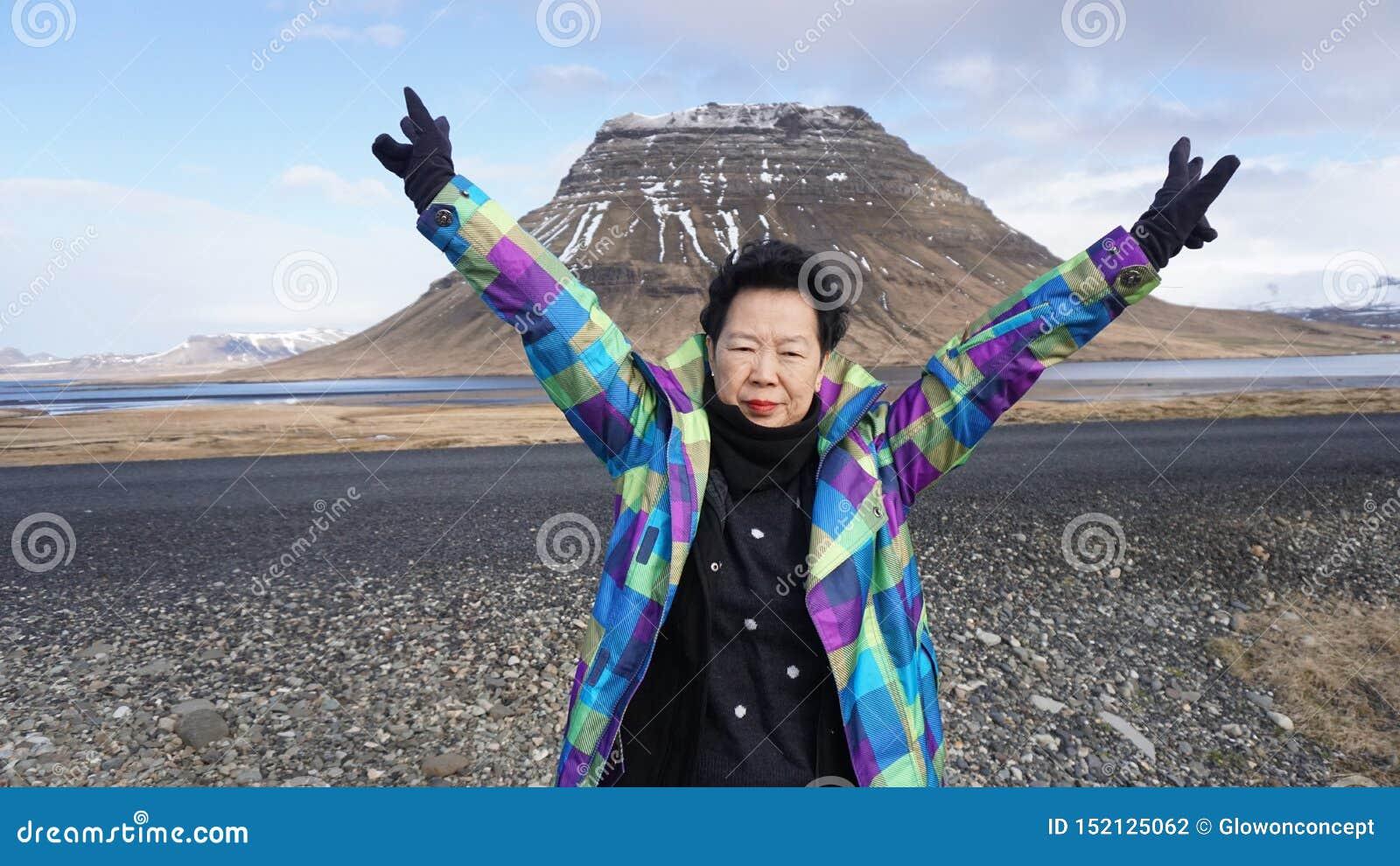 Szczęśliwa Azjatycka starsza kobieta z moutain lceland punktem zwrotnym