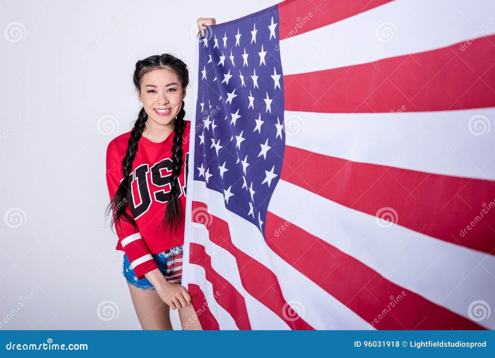 Szczęśliwa azjatykcia dziewczyna w czerwonej bluzie sportowa z usa słowa mienia flaga amerykańską odizolowywającą na popielatym