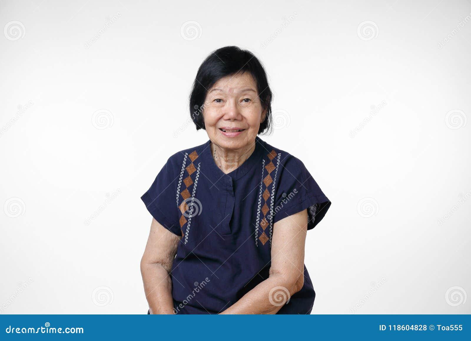 Szczęśliwa azjatykcia kobieta relaksuje w domu, odizolowywa na białym tle