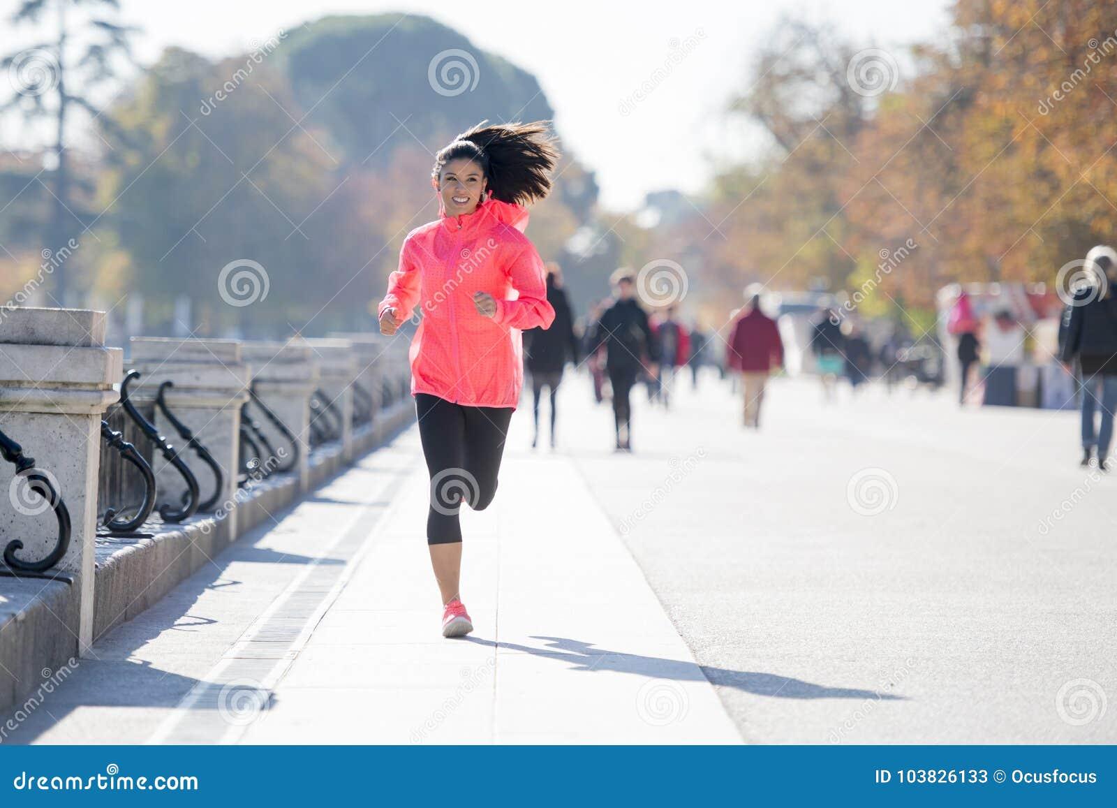 Szczęśliwa biegacz kobieta w jesieni lub zimy sportswear bieg i tr