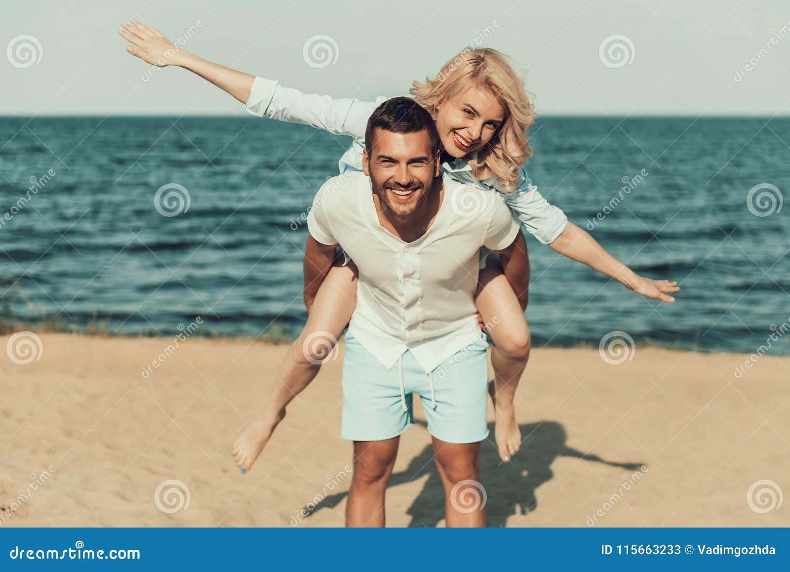Szczęśliwa blondynka obsługuje z powrotem, blisko nadmorski kobieta siedzi dalej